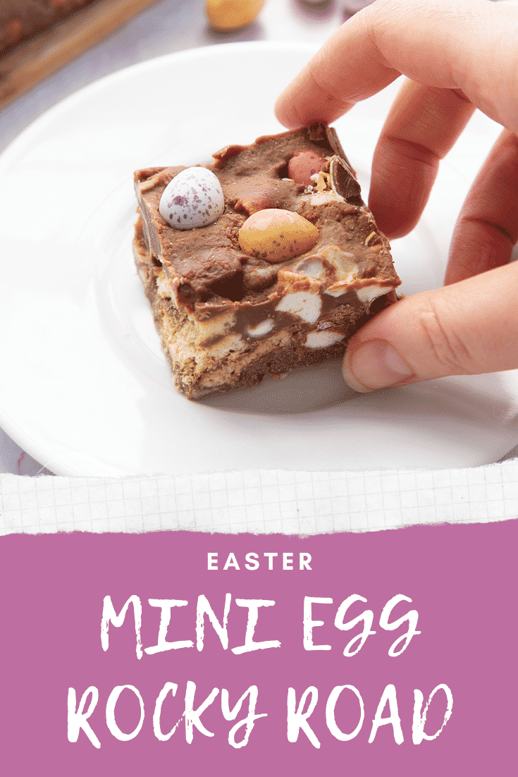 A piece of Mini Egg rocky road on a small white plate. A hand reaches for it. Caption reads: Easter Mini Egg rocky road