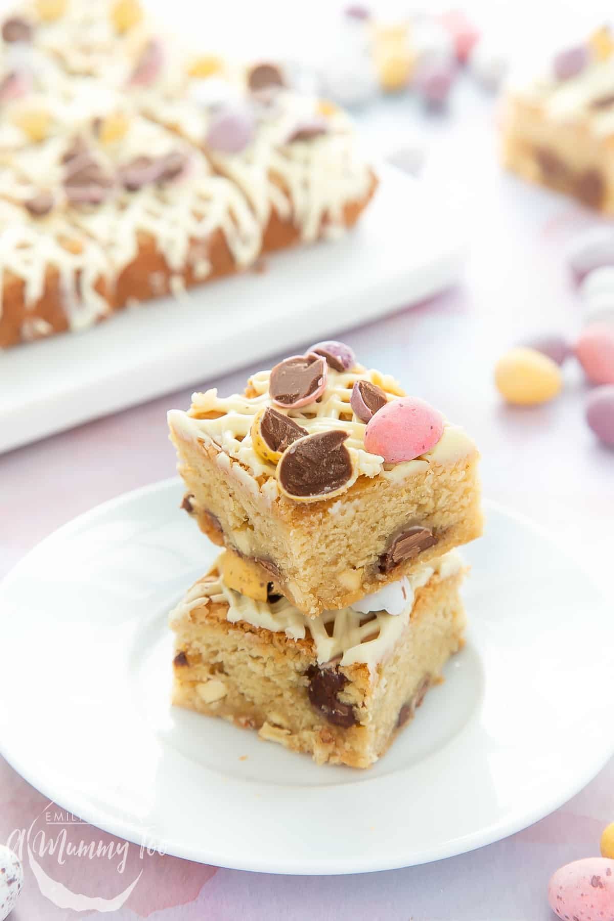 Two Mini Egg blondies on a white place. More Mini Egg blondies are on a white behind in the background.