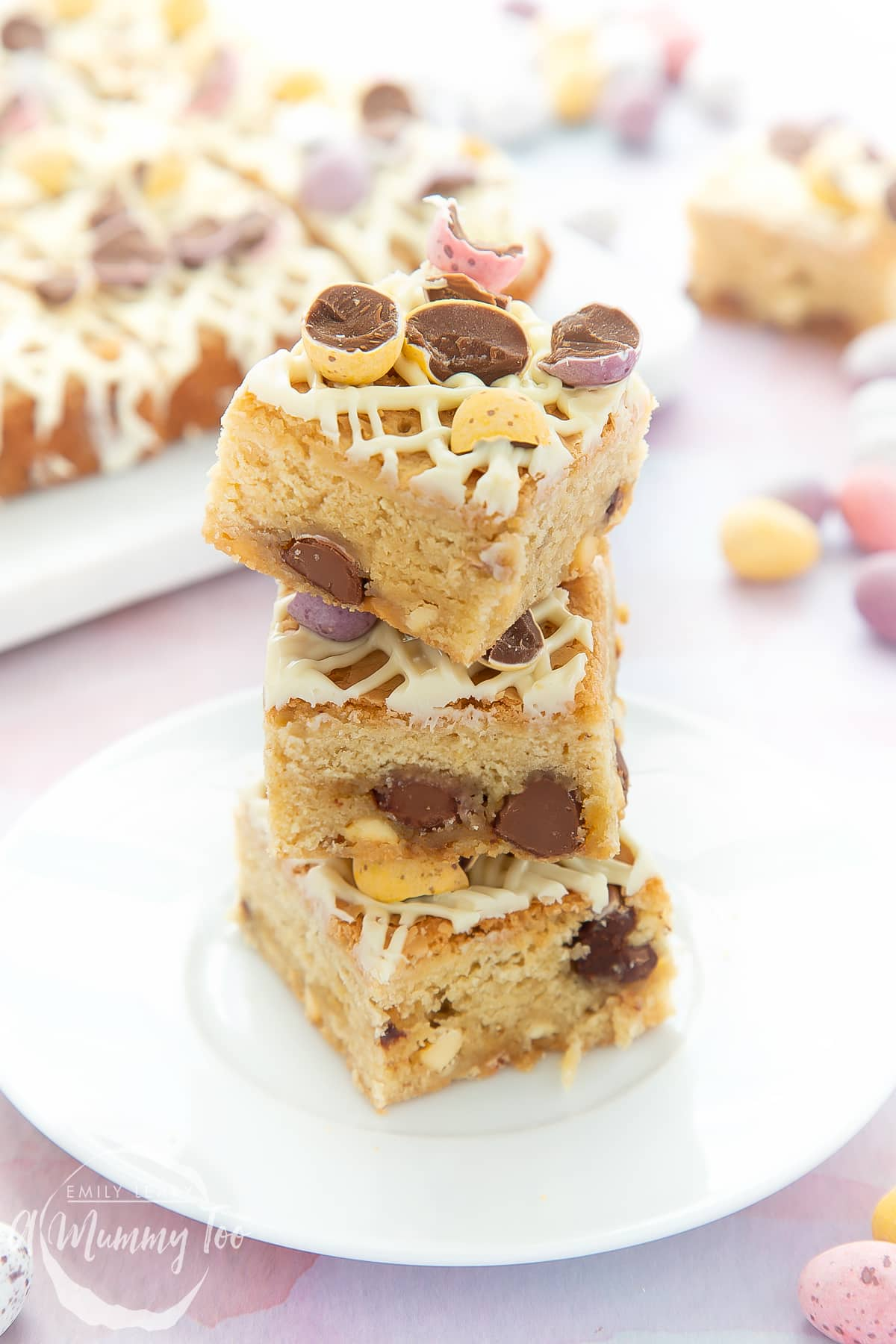 Three Mini Egg blondies on a white place. More Mini Egg blondies are on a white behind in the background.