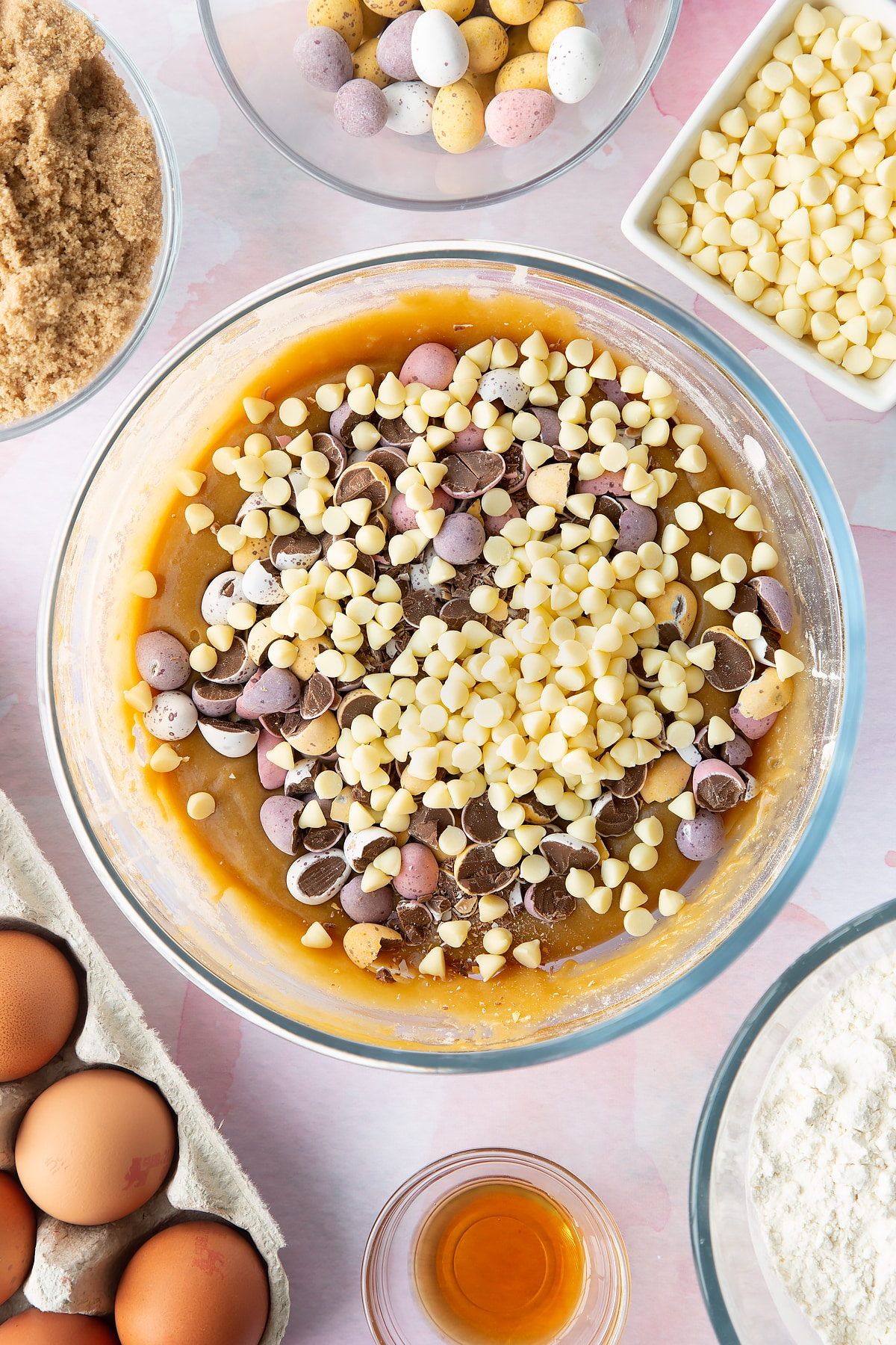 Basic blondie batter in a bowl with white choc chips and mini eggs on top. Ingredients to make Mini Egg blondies surround the bowl.