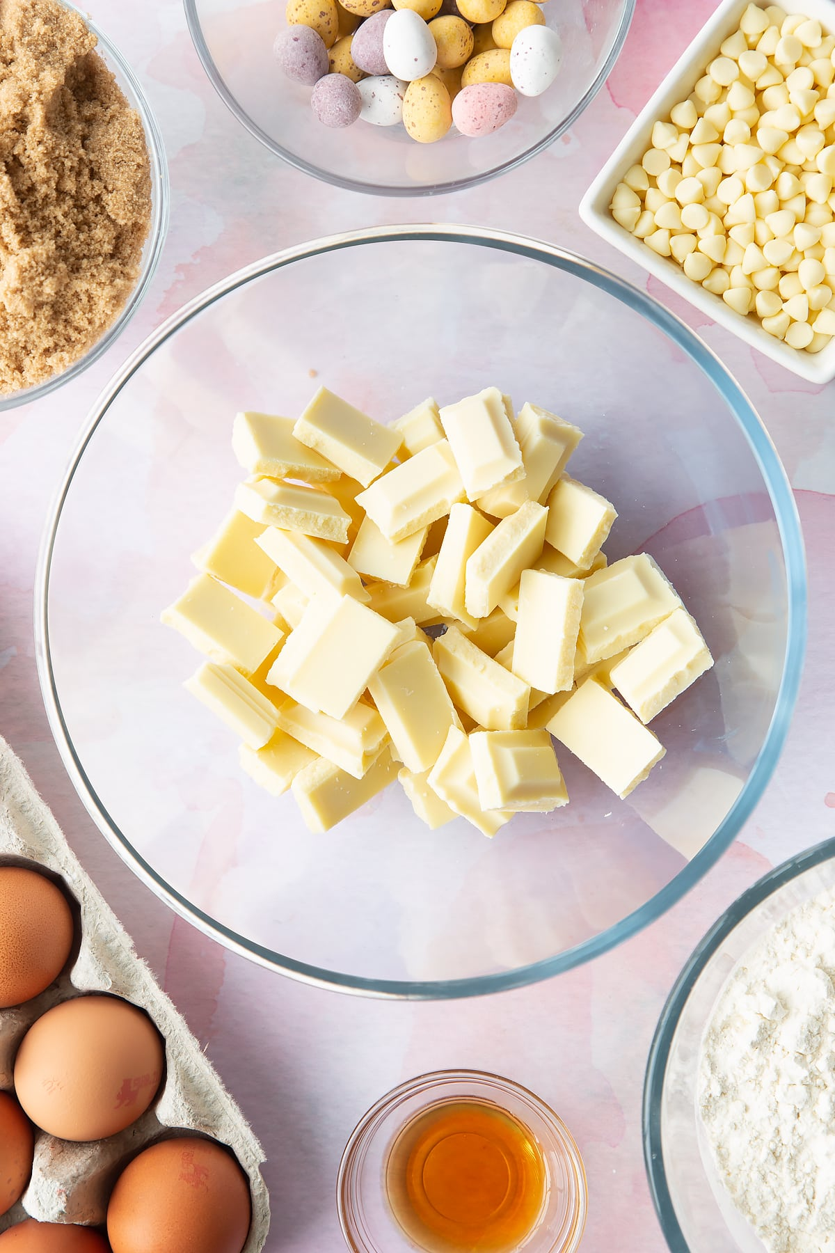 White chocolate chunks in a bowl. Ingredients to make Mini Egg blondies surround the bowl.