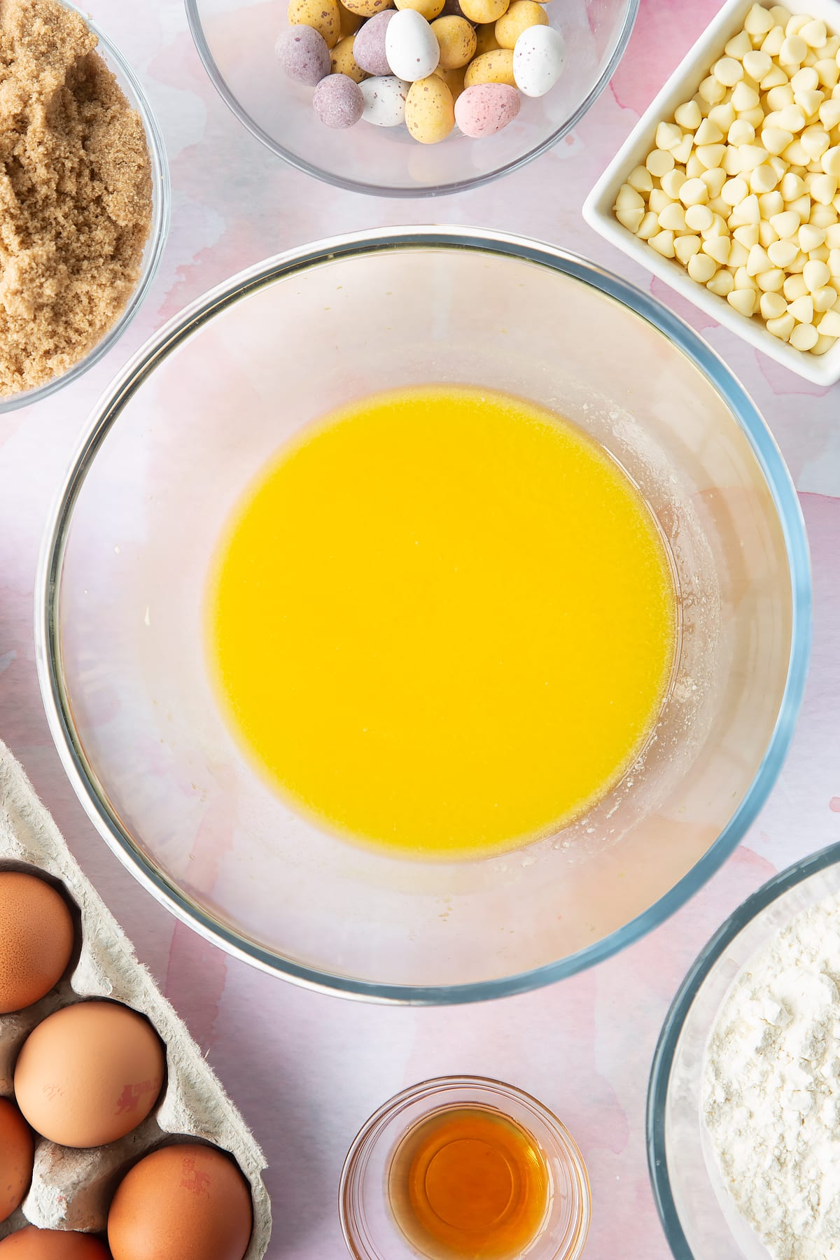Melted butter in a bowl. Ingredients to make Mini Egg blondies surround the bowl.
