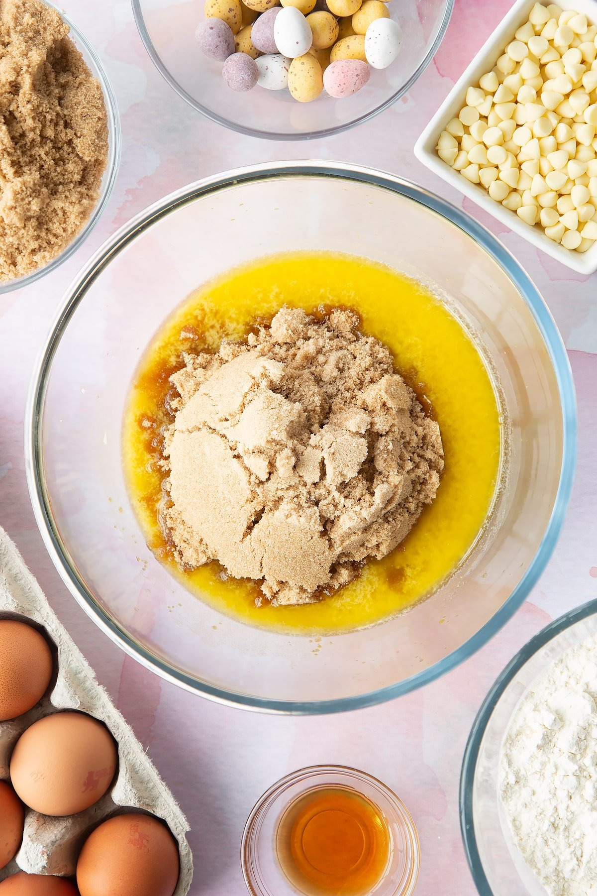 Melted butter and sugar in a bowl. Ingredients to make Mini Egg blondies surround the bowl.