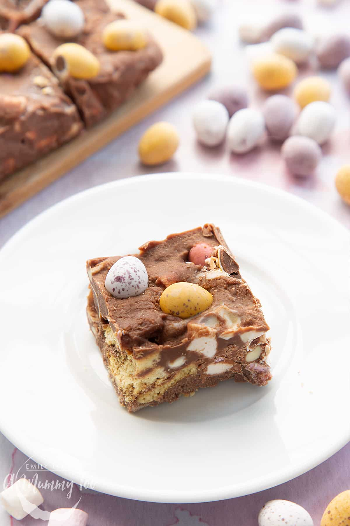 A piece of Mini Egg rocky road on a small white plate. More rocky road is in the background.