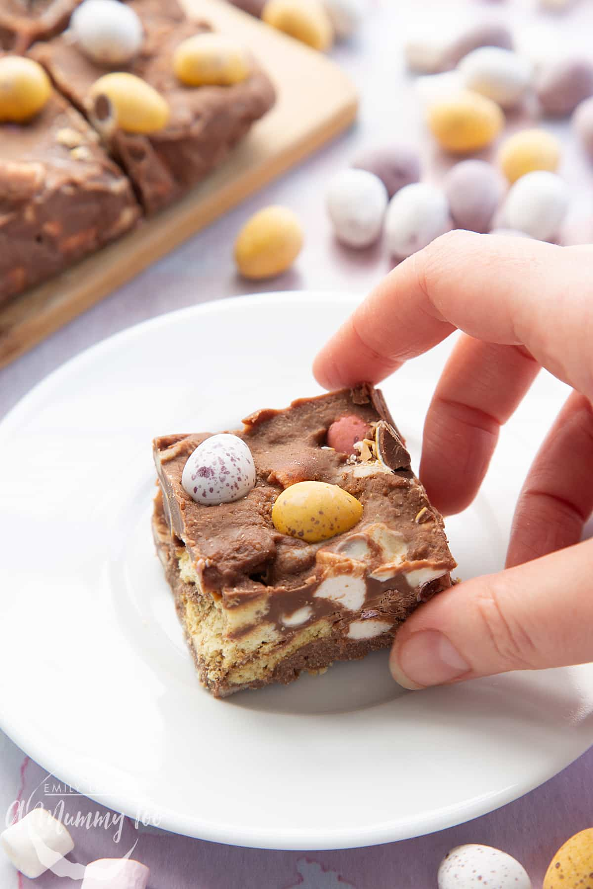 A piece of Mini Egg rocky road on a small white plate. A hand reaches to take it.