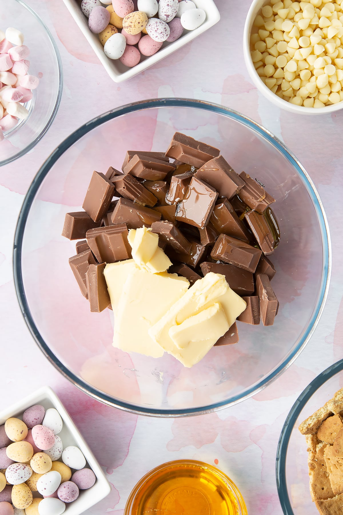 Milk chocolate, butter and golden syrup in a glass mixing bowl. Ingredients to make Mini Egg rocky road surrounds the bowl.