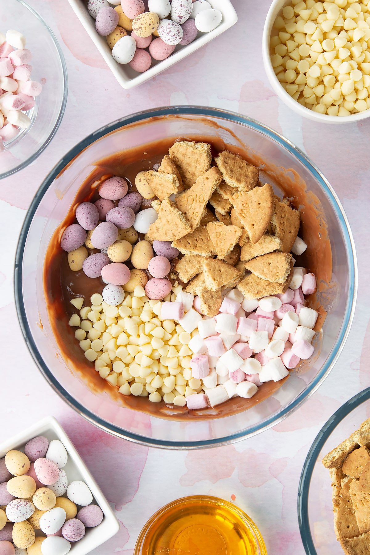 Melted milk chocolate, butter and golden syrup in a glass mixing bowl topped with white chocolate chips, digestives, marshmallows and Mini Eggs. Ingredients to make Mini Egg rocky road surrounds the bowl.