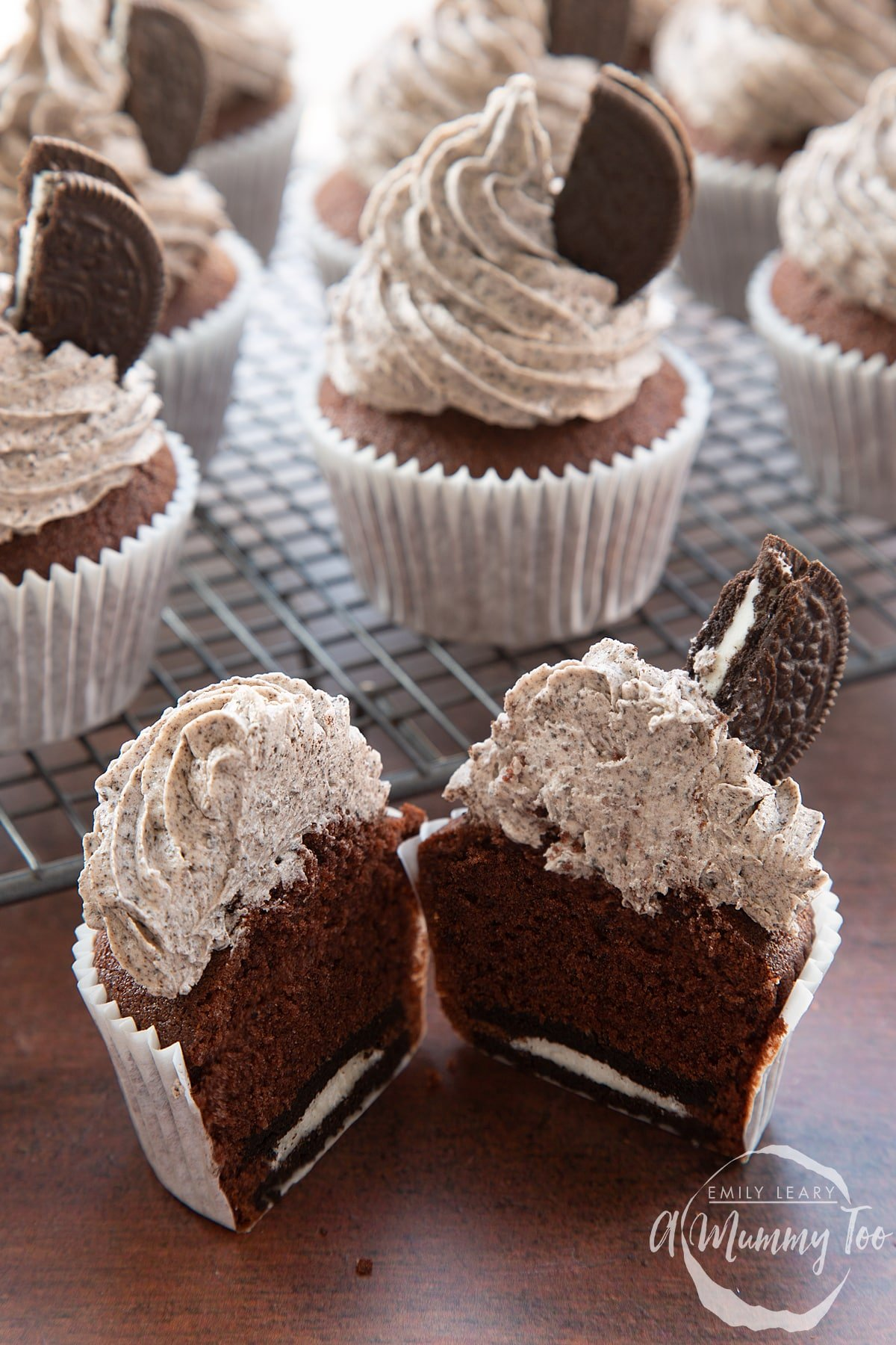 Front view shot of a chocolate cupcake with orea frosting cut in half