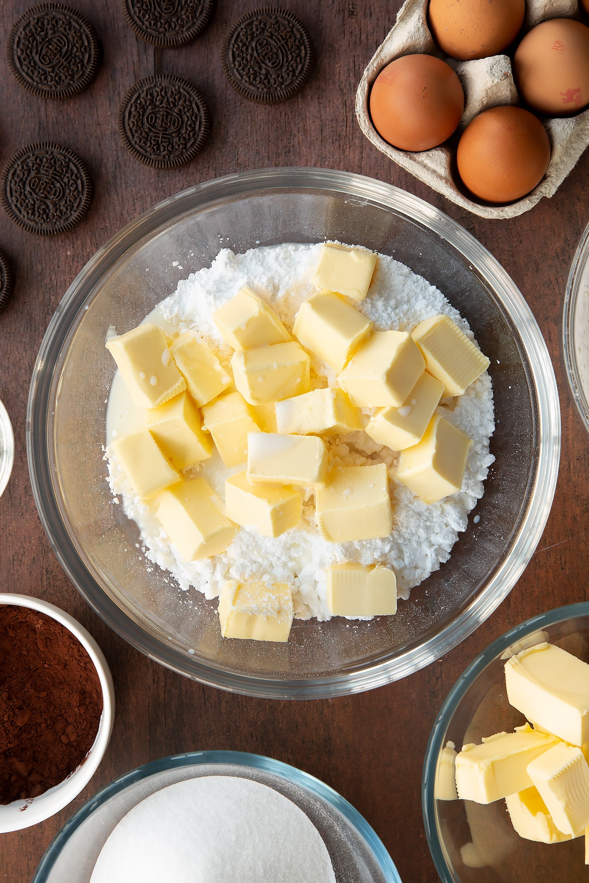 Overhead shot of butter chunks and icing sugar in a bowl