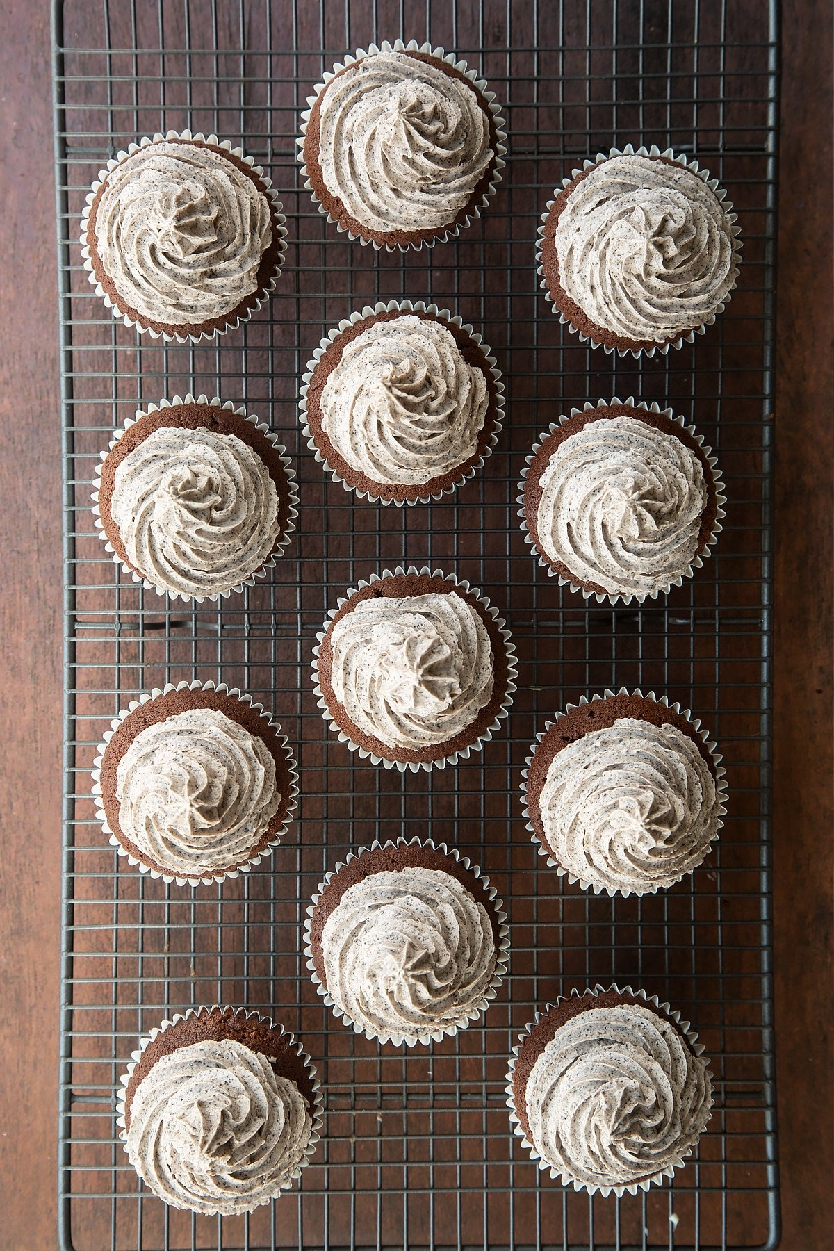 Overhead shot of chocolate cupcakes topped with oreo buttercream on a wire rack