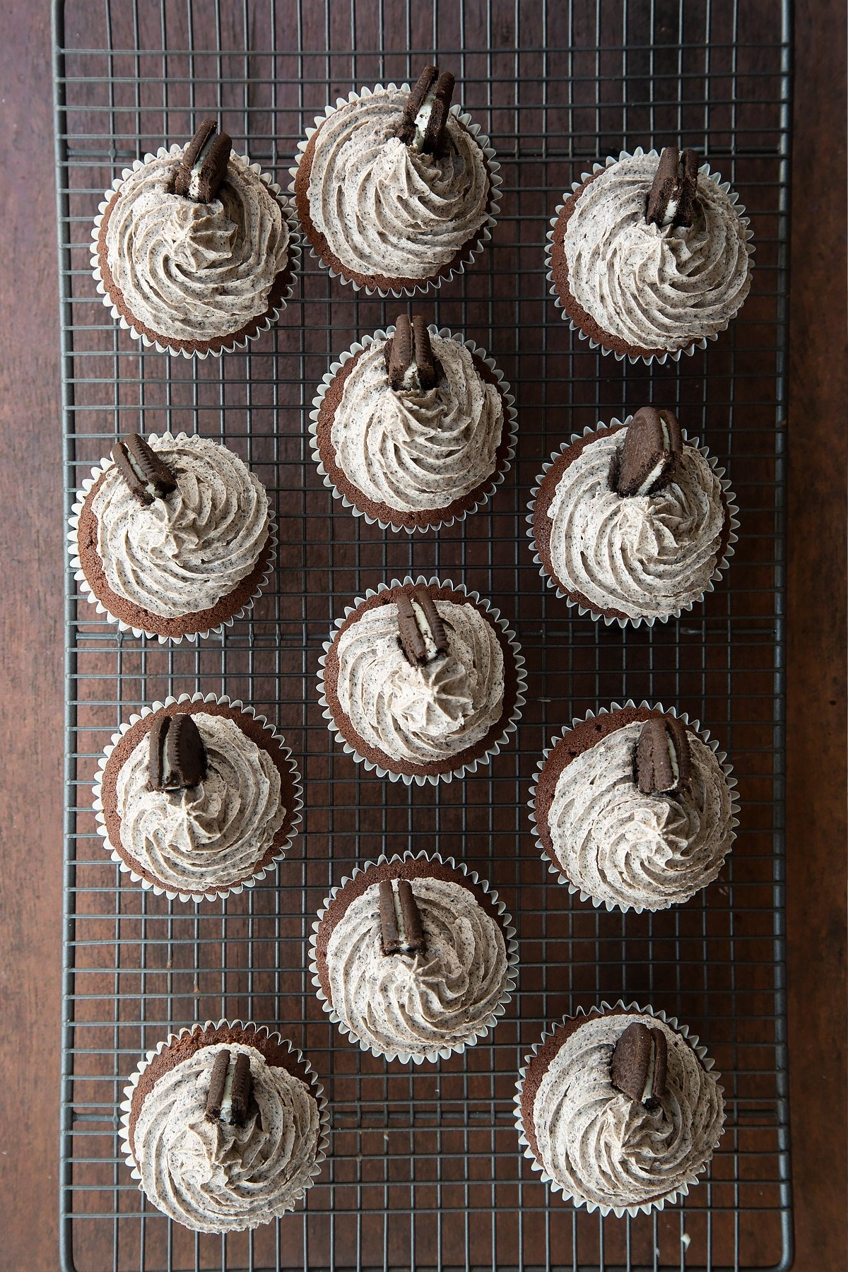 Overhead shot of oreo butter cream topped chocolate cupcakes with half an oreo in the side on a wire rack
