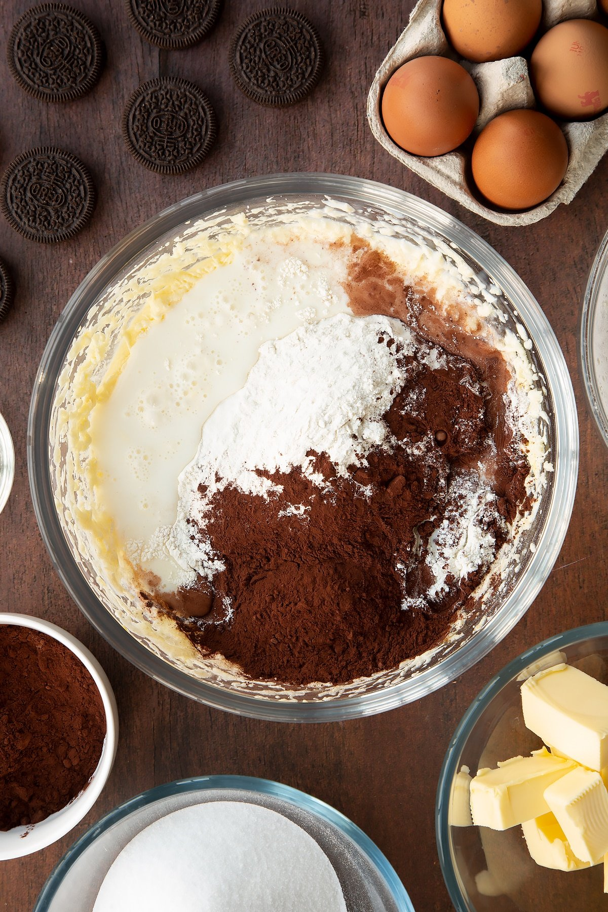 Overhead shot of batter mix with flour, milk, cocoa powder and baking powder in a large clear bowl