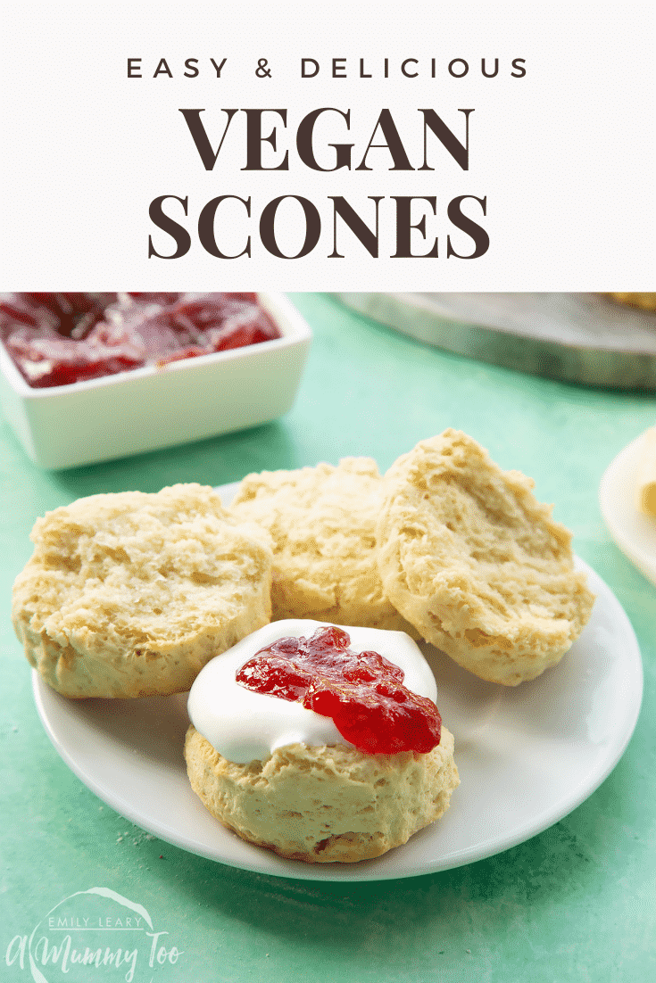 Two dairy free scones on a white plate. They are split in half and one is topped with jam and vegan whipped cream. Caption reads: easy & delicious vegan scones