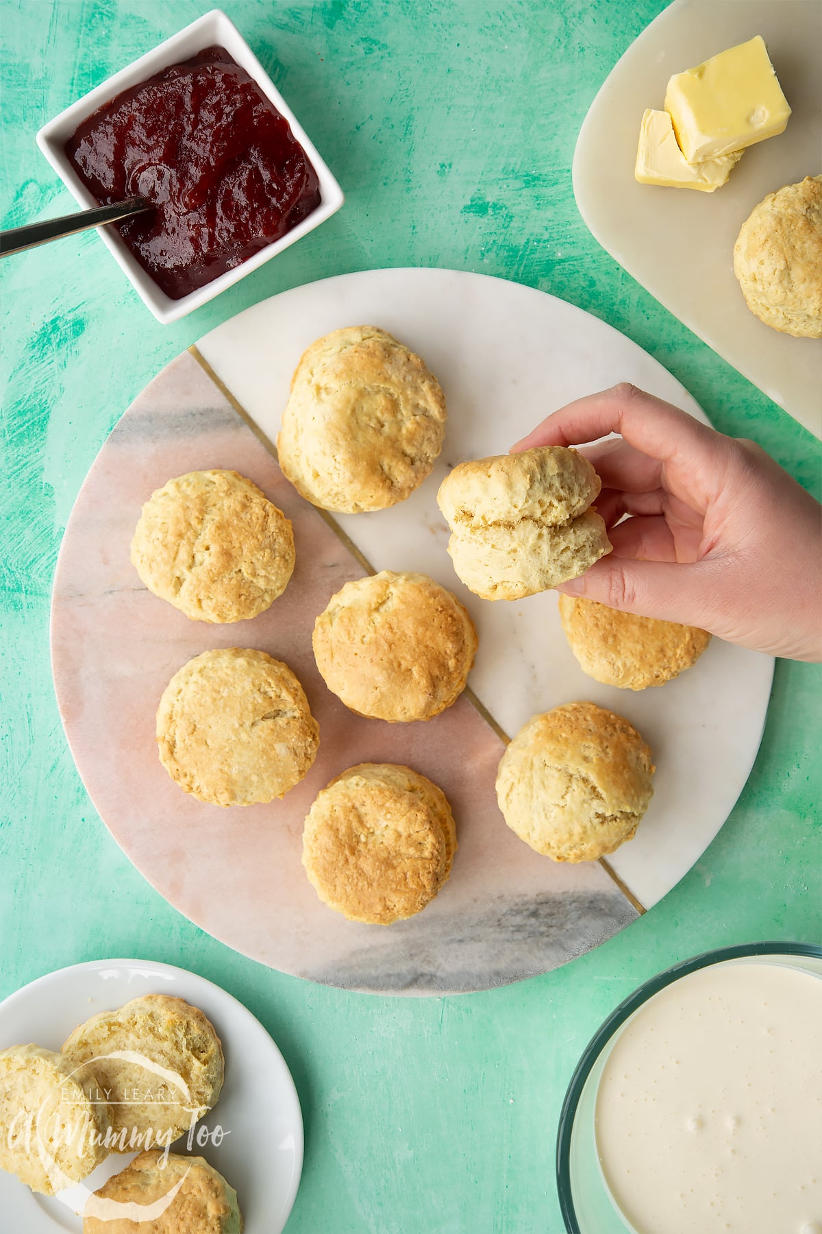 Dairy free scones on a round marble board plate. A hand holds one.