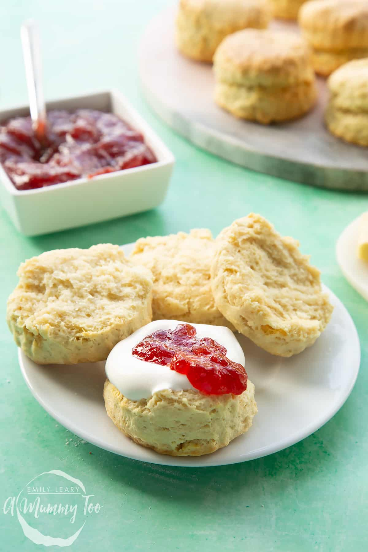 Two dairy free scones on a white plate. They are split in half and one is topped with jam and vegan whipped cream.