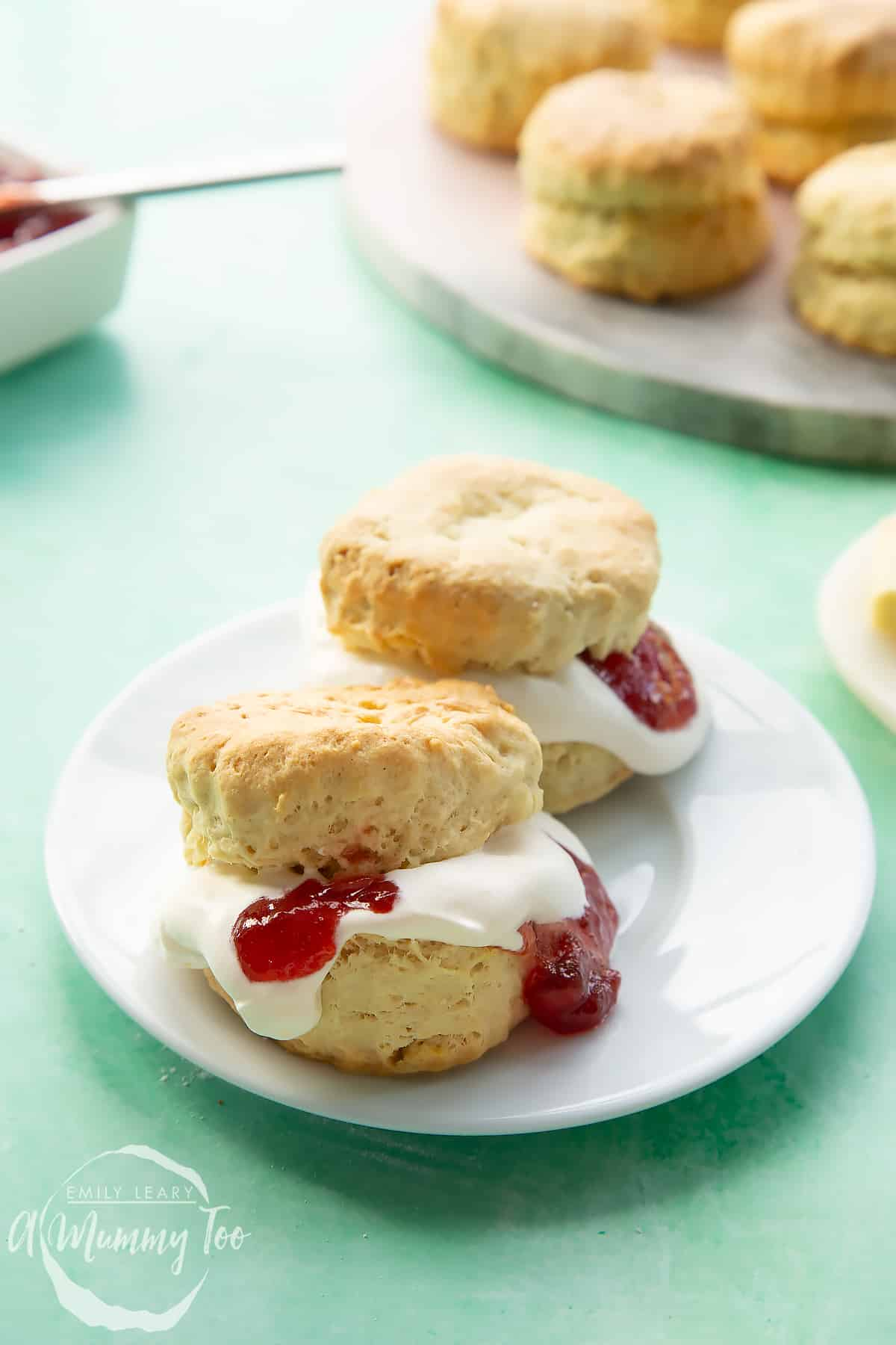 Two dairy free scones on a white plate. They are filled with jam and vegan whipped cream.