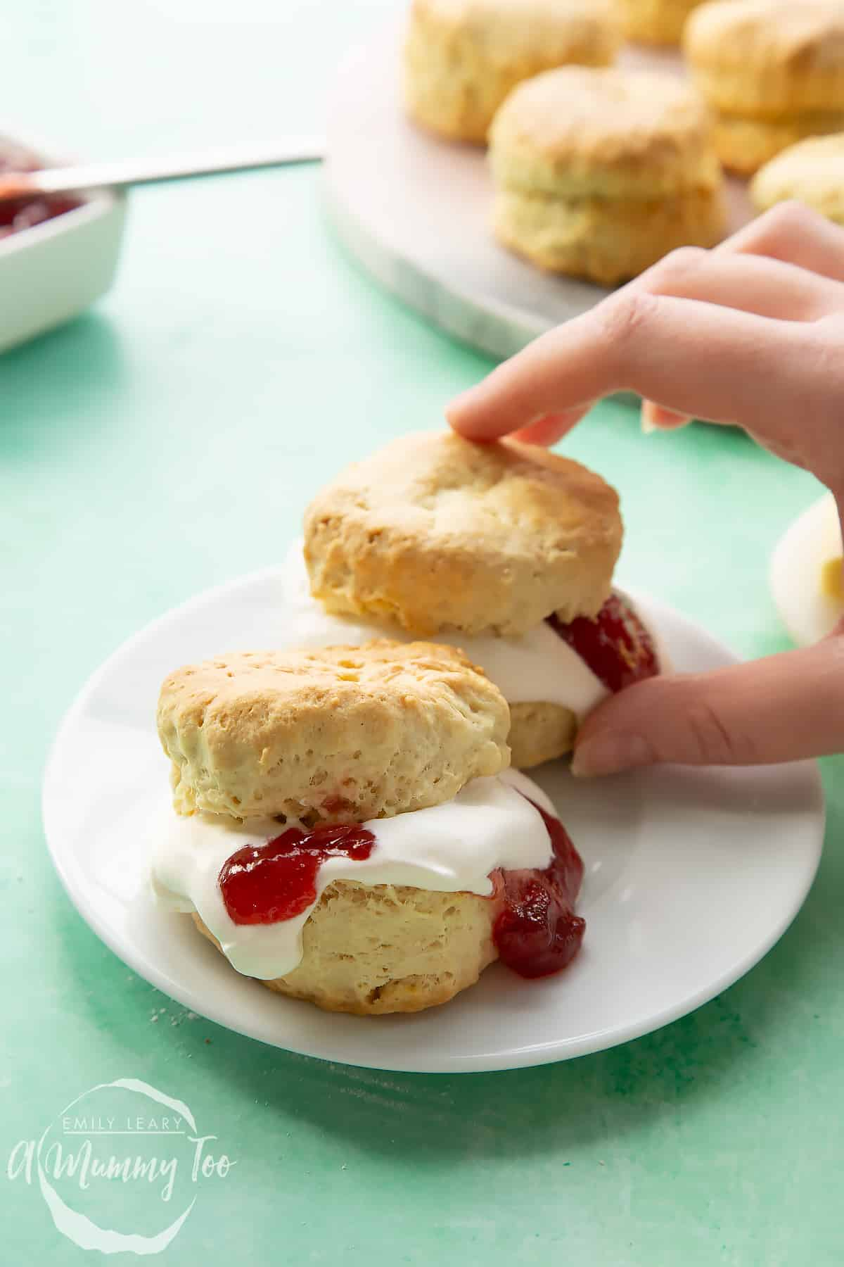 Two dairy free scones on a white plate. They are filled with jam and vegan whipped cream. A hand reaches for one.