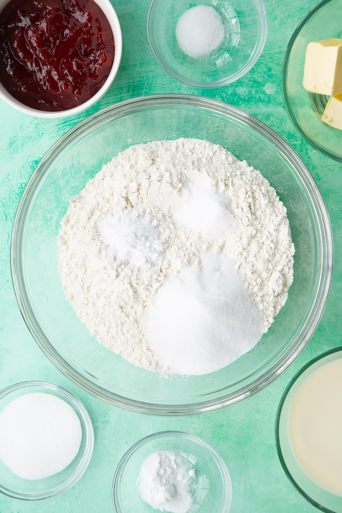Flour, sugar, salt and bicarbonate of soda in a bowl. Ingredients to make dairy free scones surround the bowl.