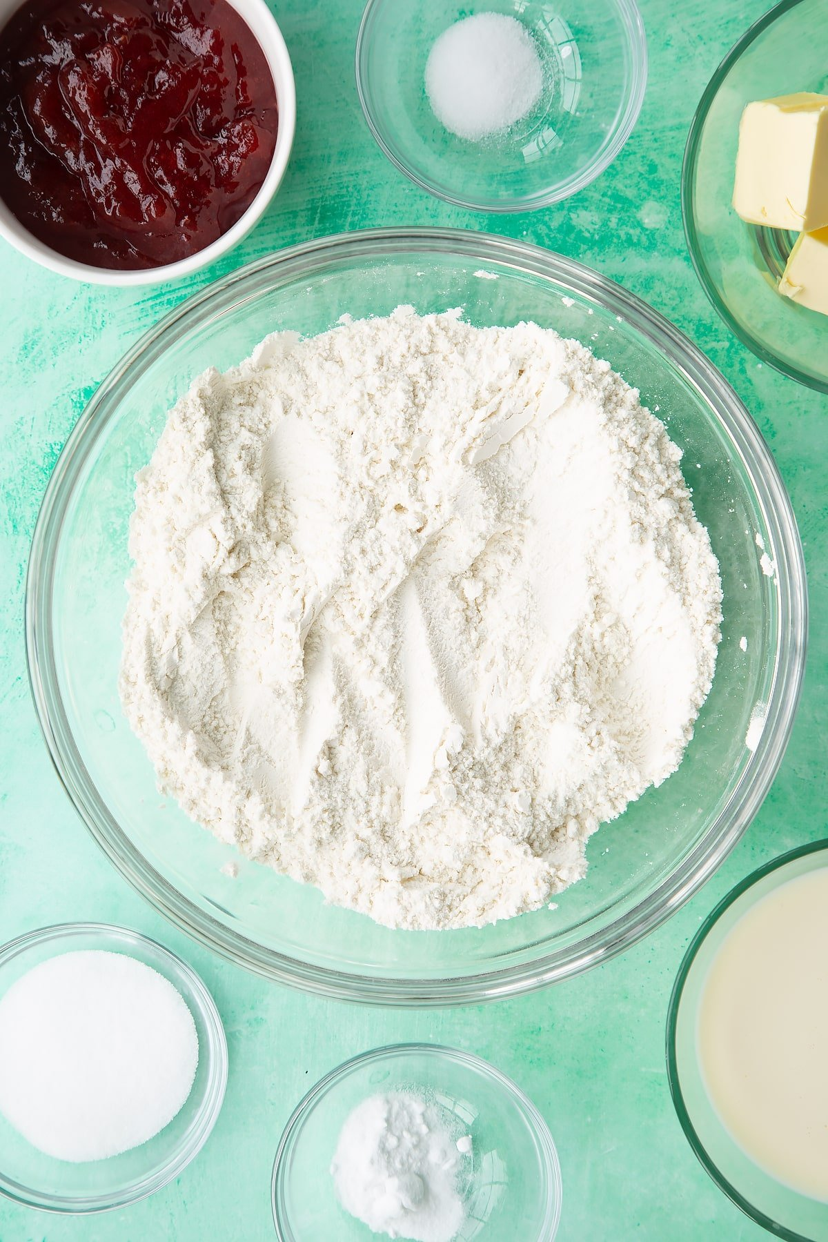 Flour, sugar, salt and bicarbonate of soda mixed together in a bowl. Ingredients to make dairy free scones surround the bowl.