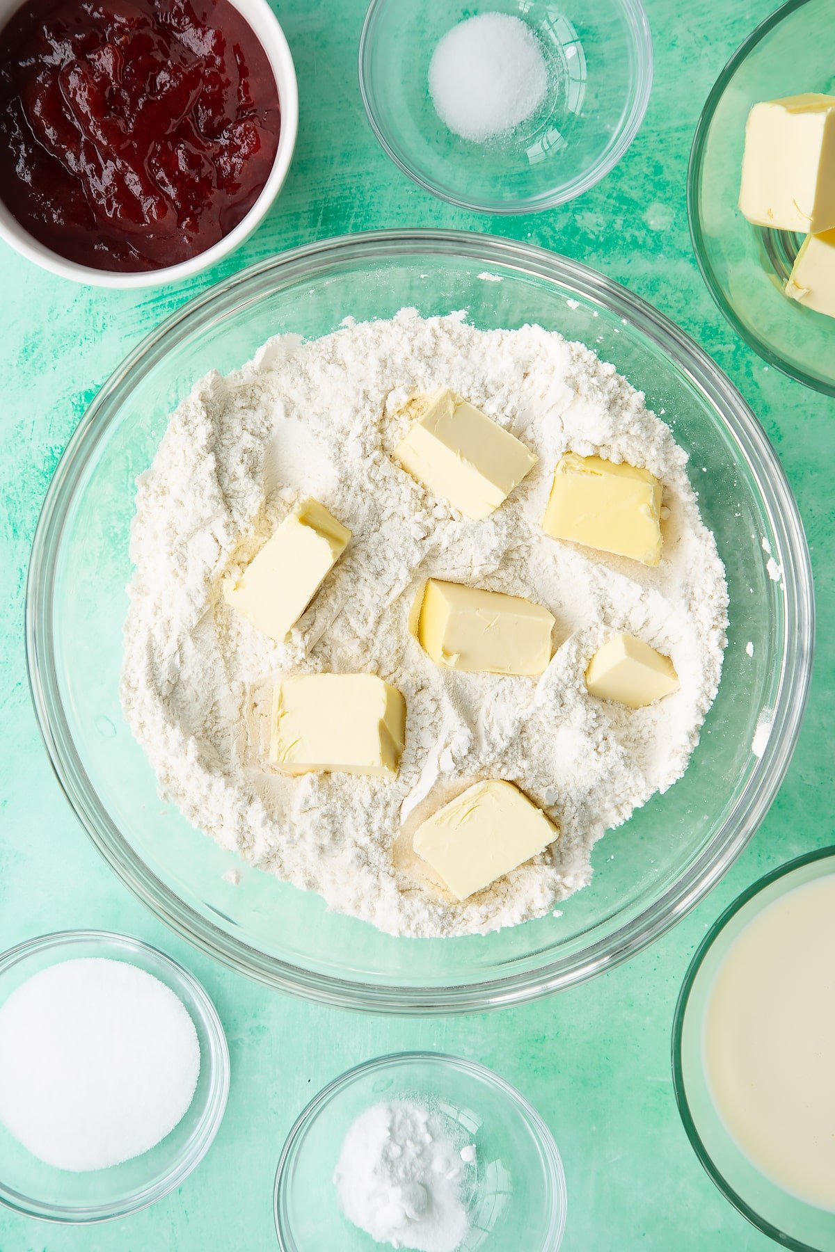 Flour, sugar, salt and bicarbonate of soda mixed together in a bowl with cubed vegan butter on top. Ingredients to make dairy free scones surround the bowl.
