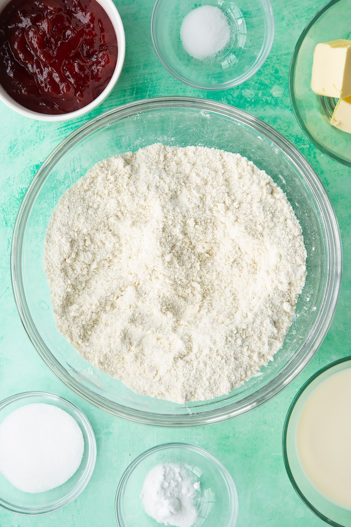 Flour, sugar, salt, bicarbonate of soda and vegan butter rubbed together in a bowl. Ingredients to make dairy free scones surround the bowl.