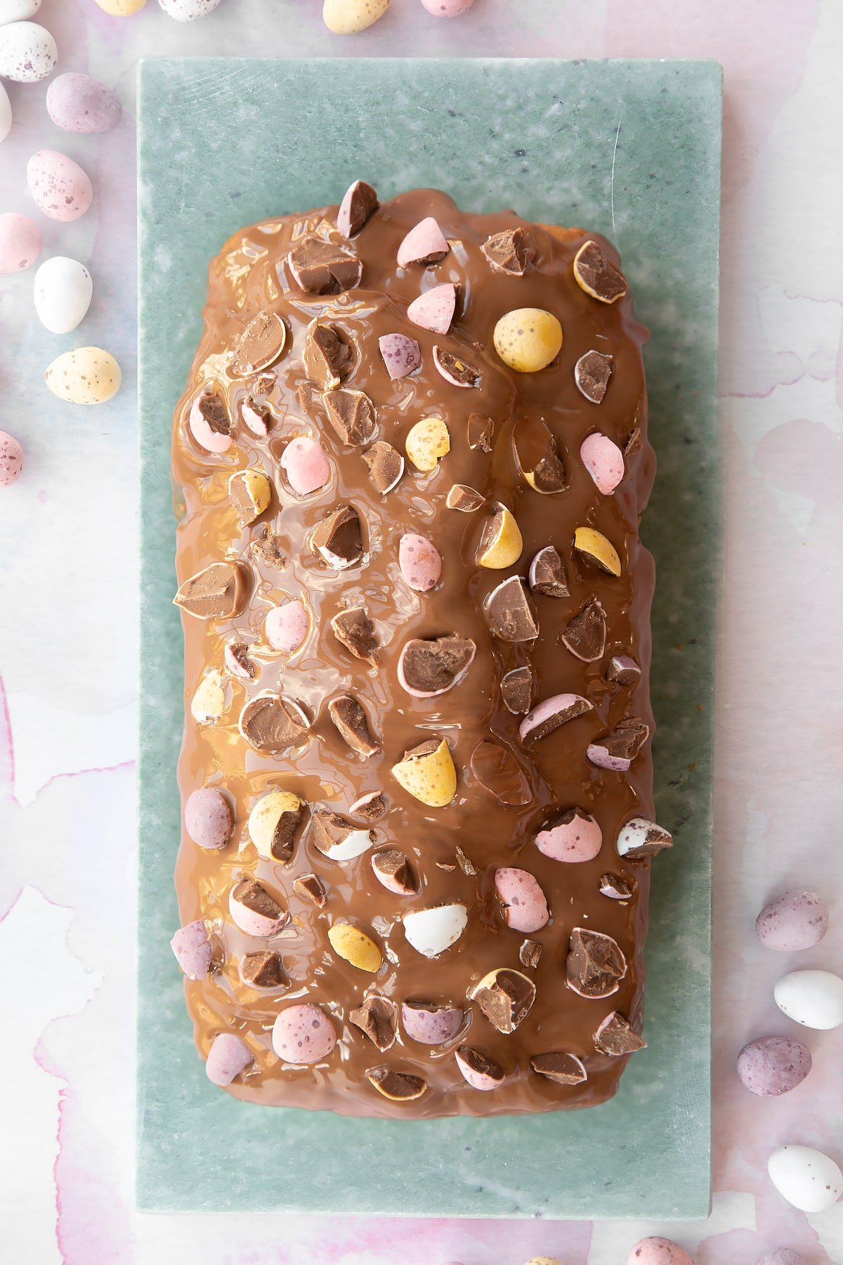 Easter banana bread decorated with milk chocolate and chopped Mini Eggs on a long grey marble board.