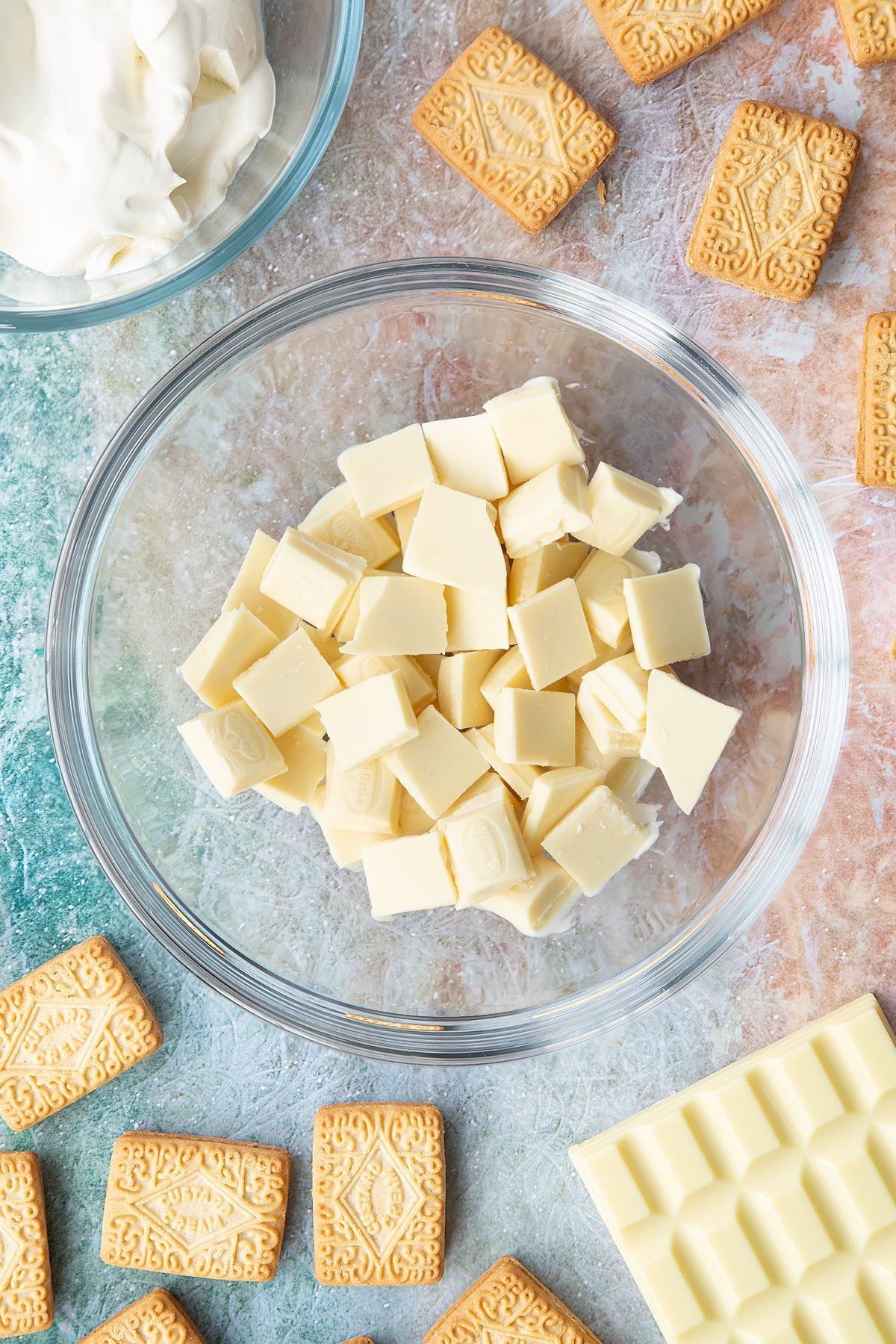 Overhead shot of pieces of white chocolate in a large clear bowl
