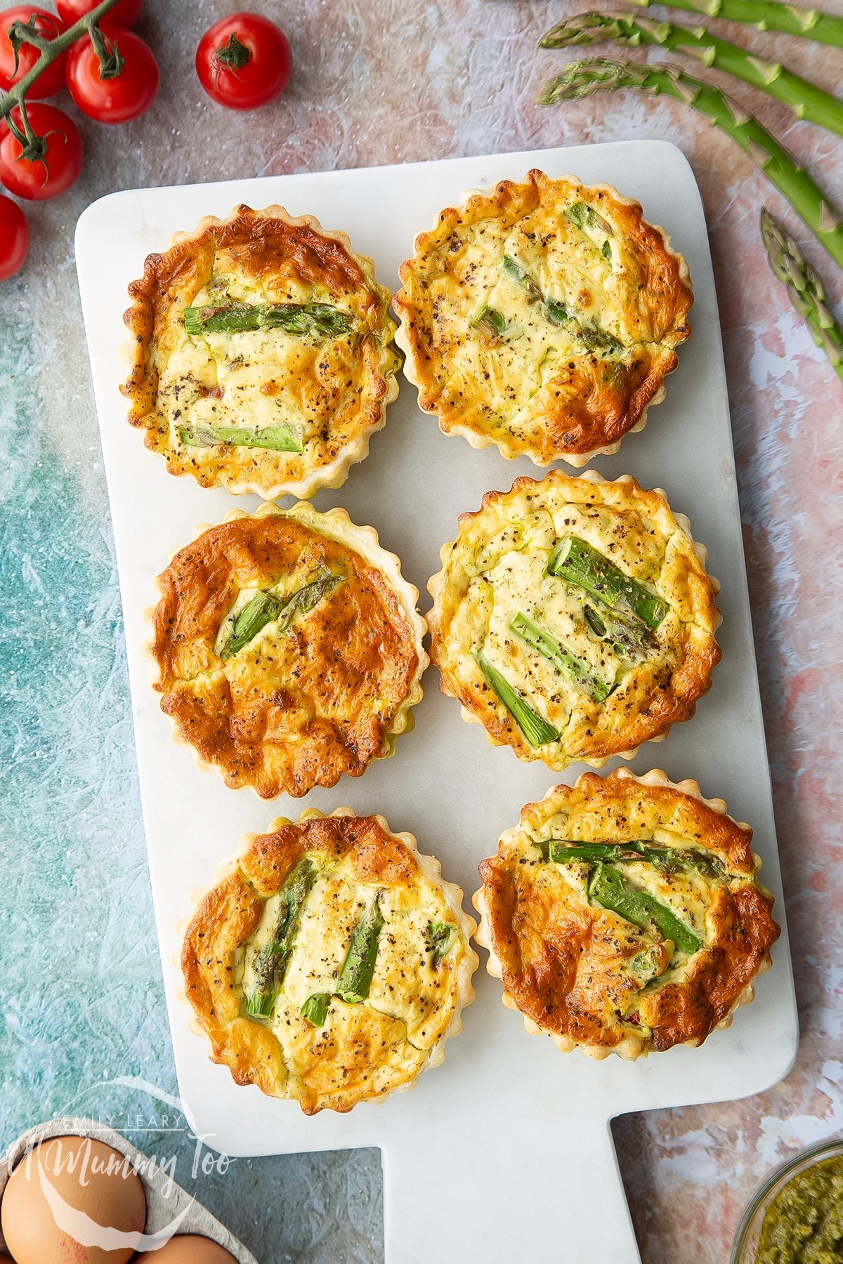 Asparagus tartlets on a white marble board. Shown from above.