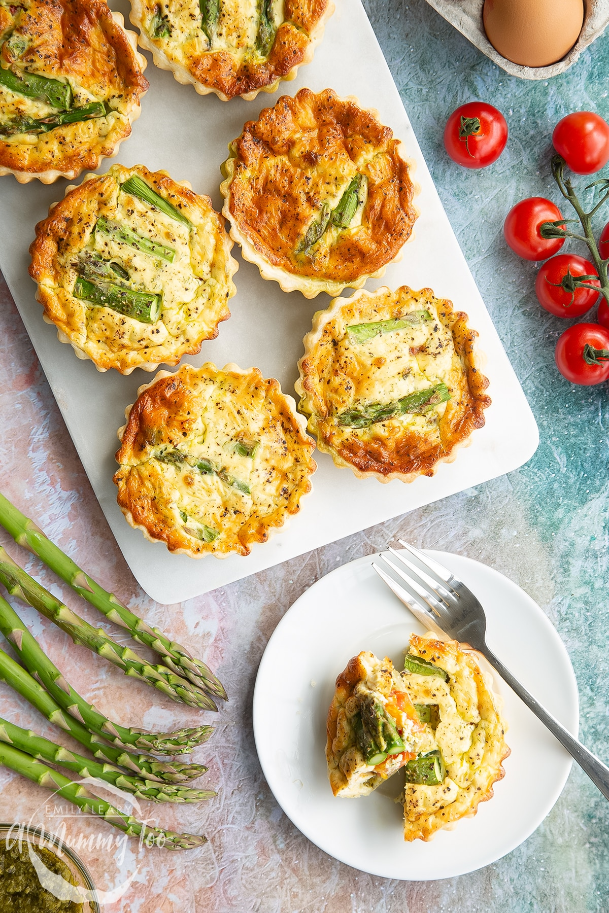 Asparagus tartlets on a white marble board. One is on a white plate with a fork. It has been cut up. Shown from above.