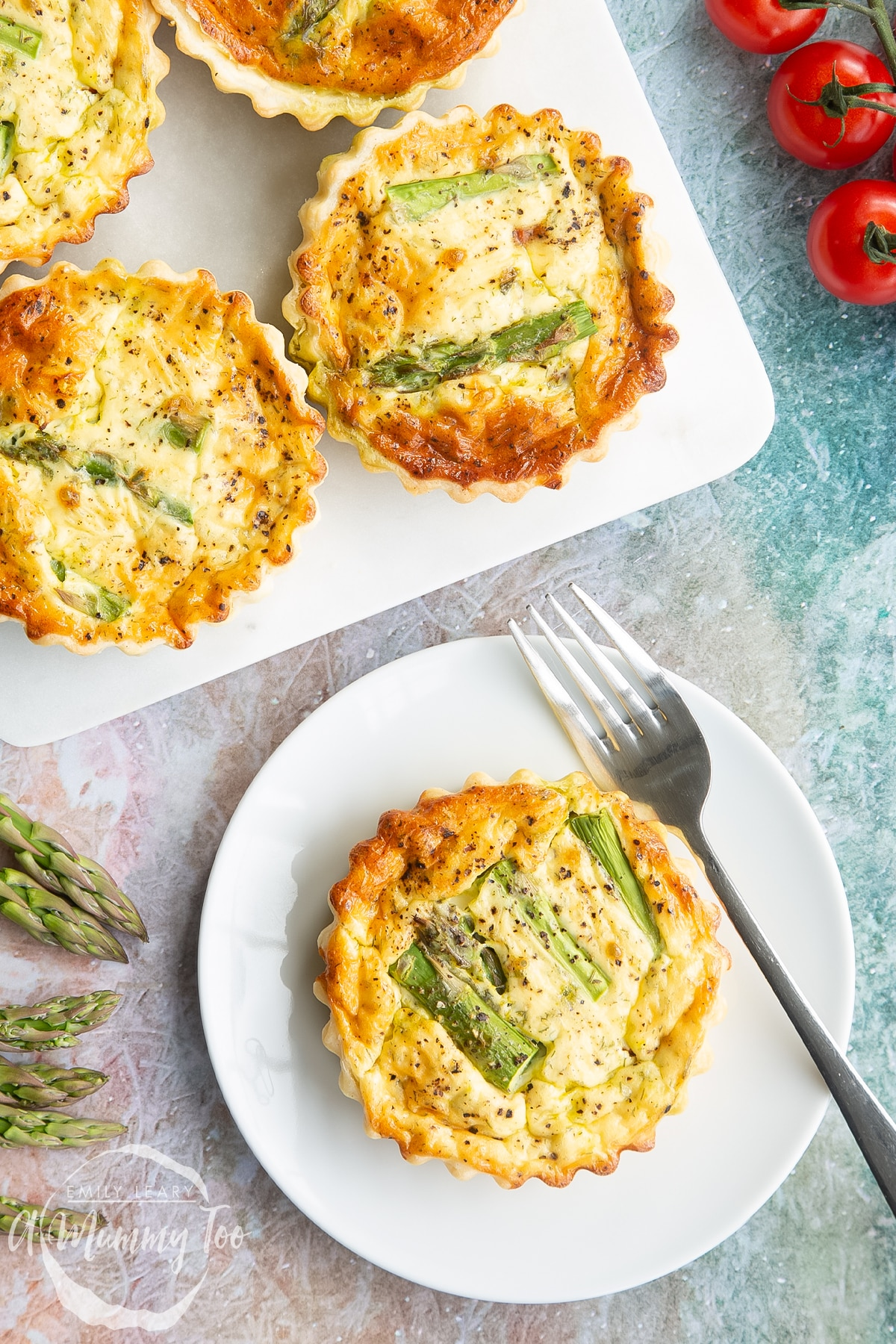 Asparagus tartlets on a white plate with a fork in close up.