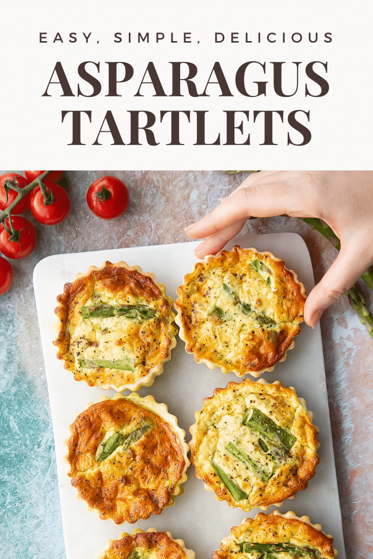 Asparagus tartlets on a white marble board. A hand reaches for one. Caption reads: easy, simple, delicious asparagus tartlets