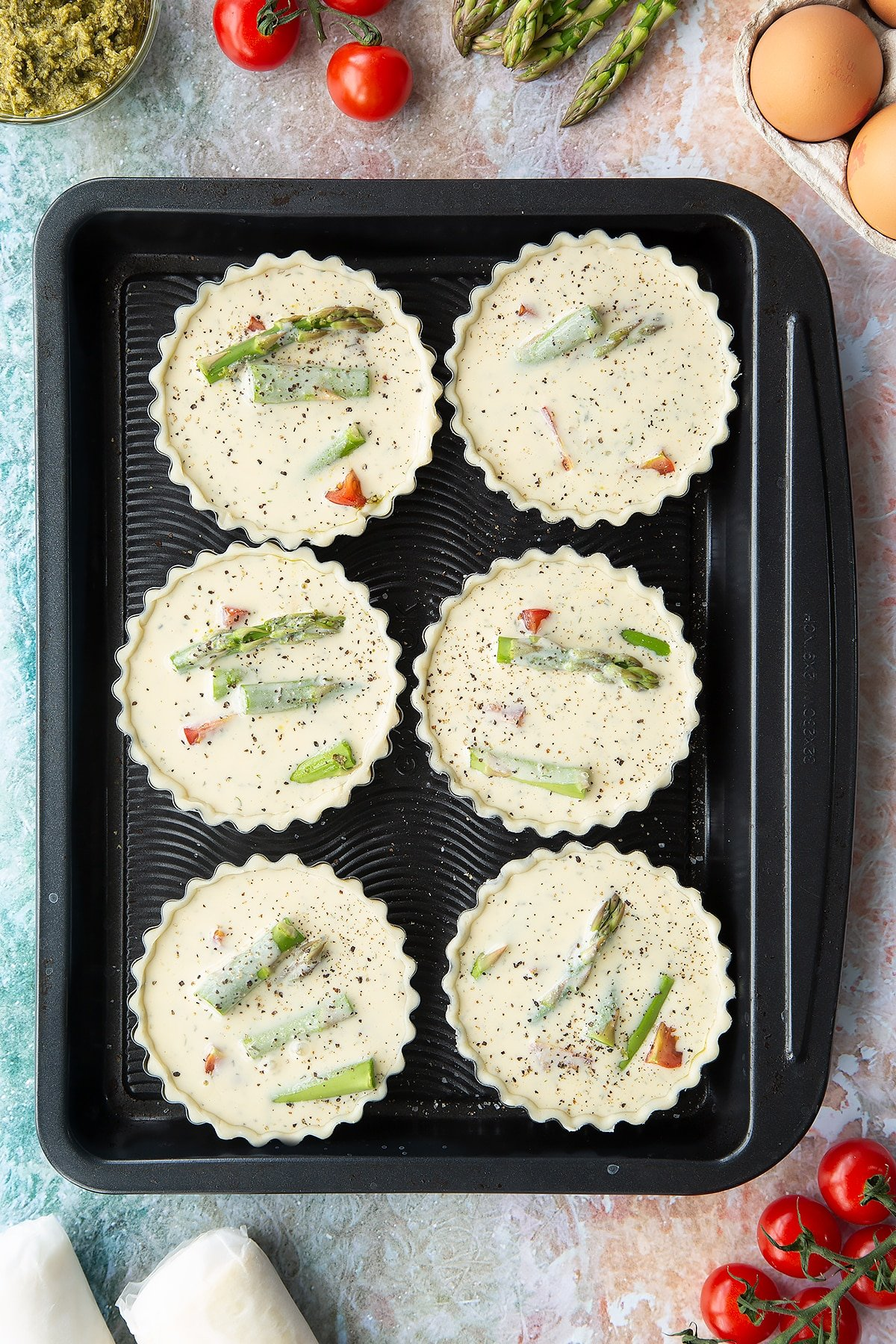 Six tartlet tins on a baking tray. Pastry is fitted in the tins, which is filled with tart filling, cherry tomato and asparagus pieces. Ingredients to make asparagus tartlets surround the tray.