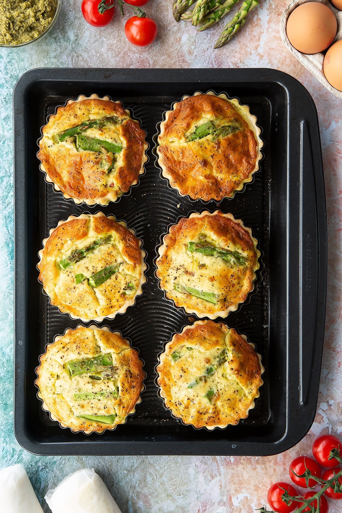 Six asparagus tartlets on a baking tray. Shown from above.