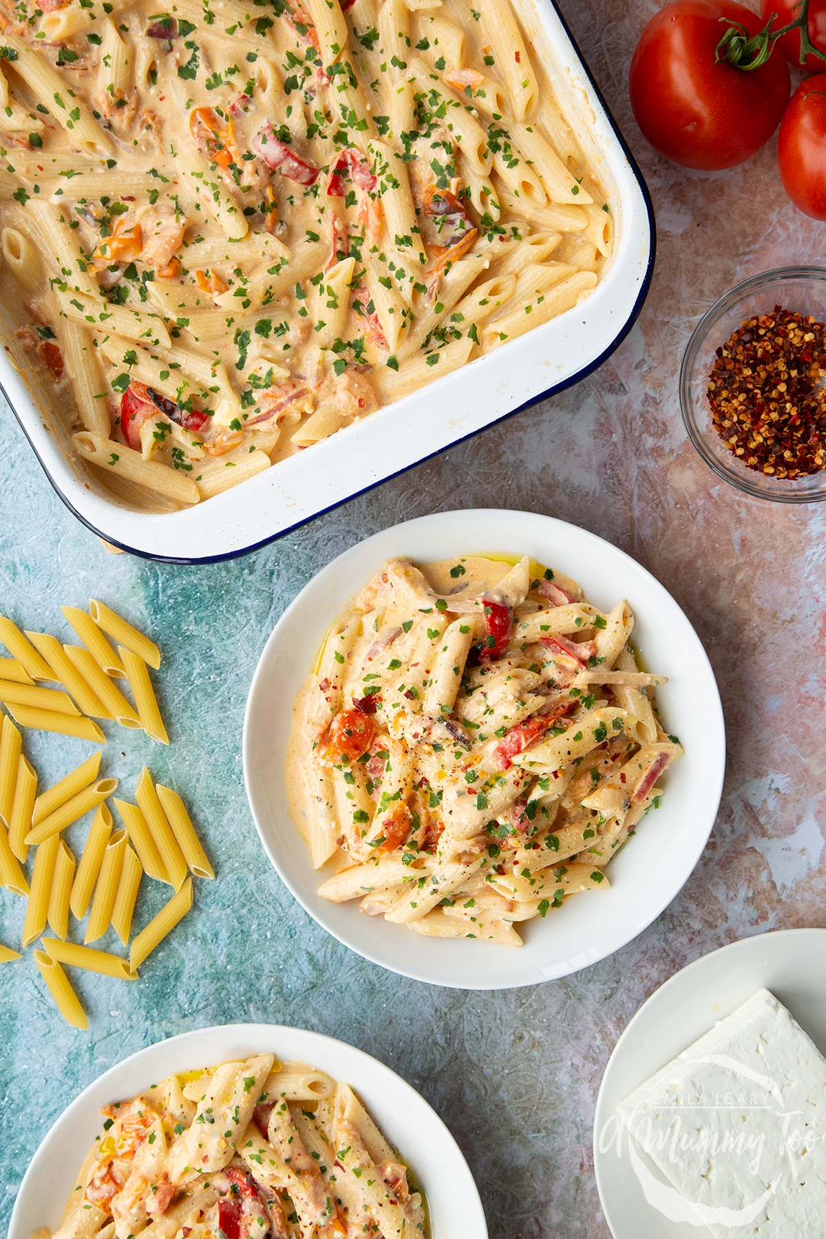 Baked feta pasta in a white bowl, garnished with parsley and chilli flakes. A tray of more pasta is shown beside it.