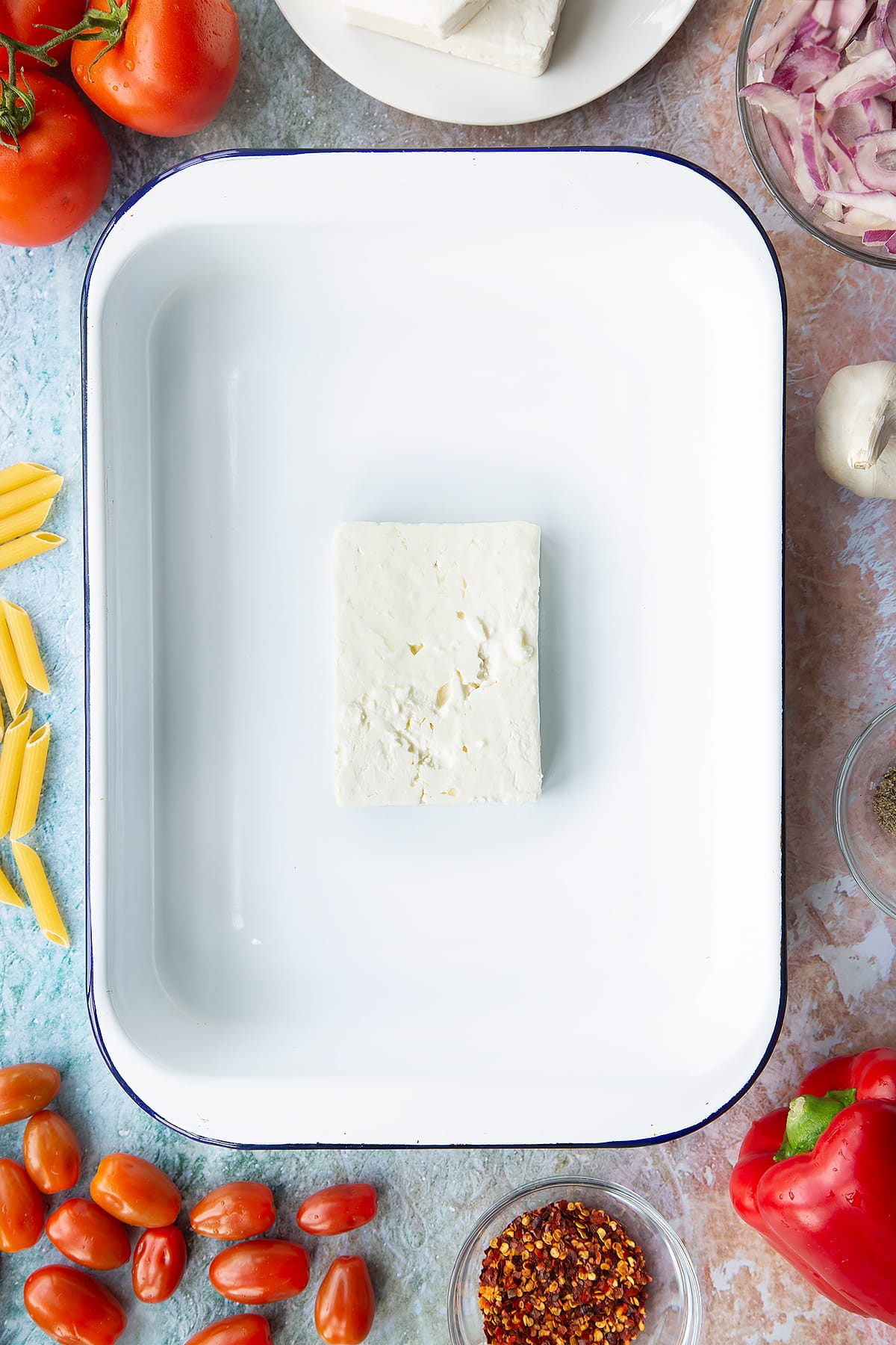 A block of feta in a large white roasting tray. Ingredients to make baked feta pasta surround the tray.