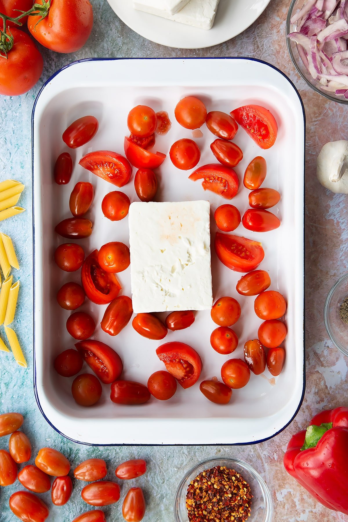 A block of feta surrounded by tomatoes in a large white roasting tray. Ingredients to make baked feta pasta surround the tray.
