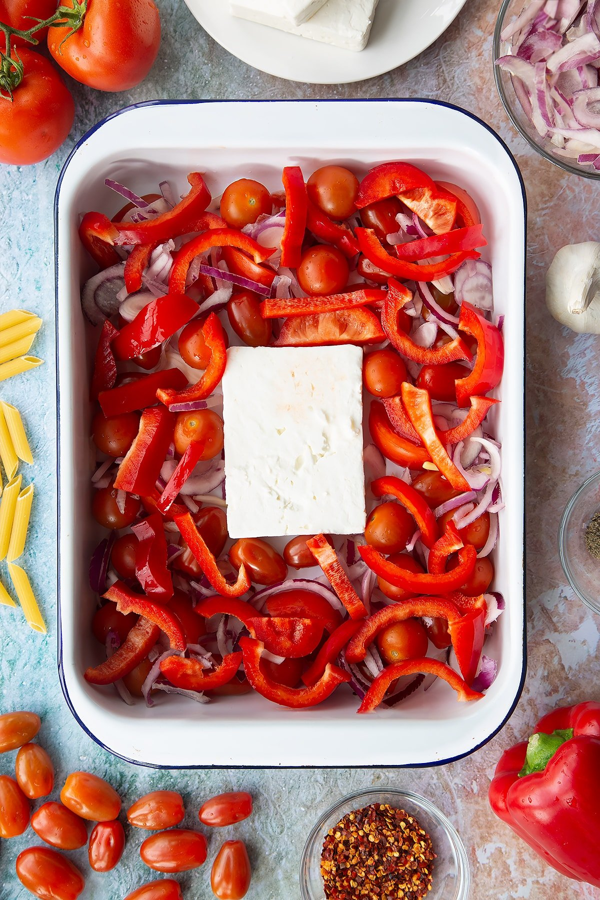 A block of feta surrounded by tomatoes, red pepper and red onion slices in a large white roasting tray. Ingredients to make baked feta pasta surround the tray.