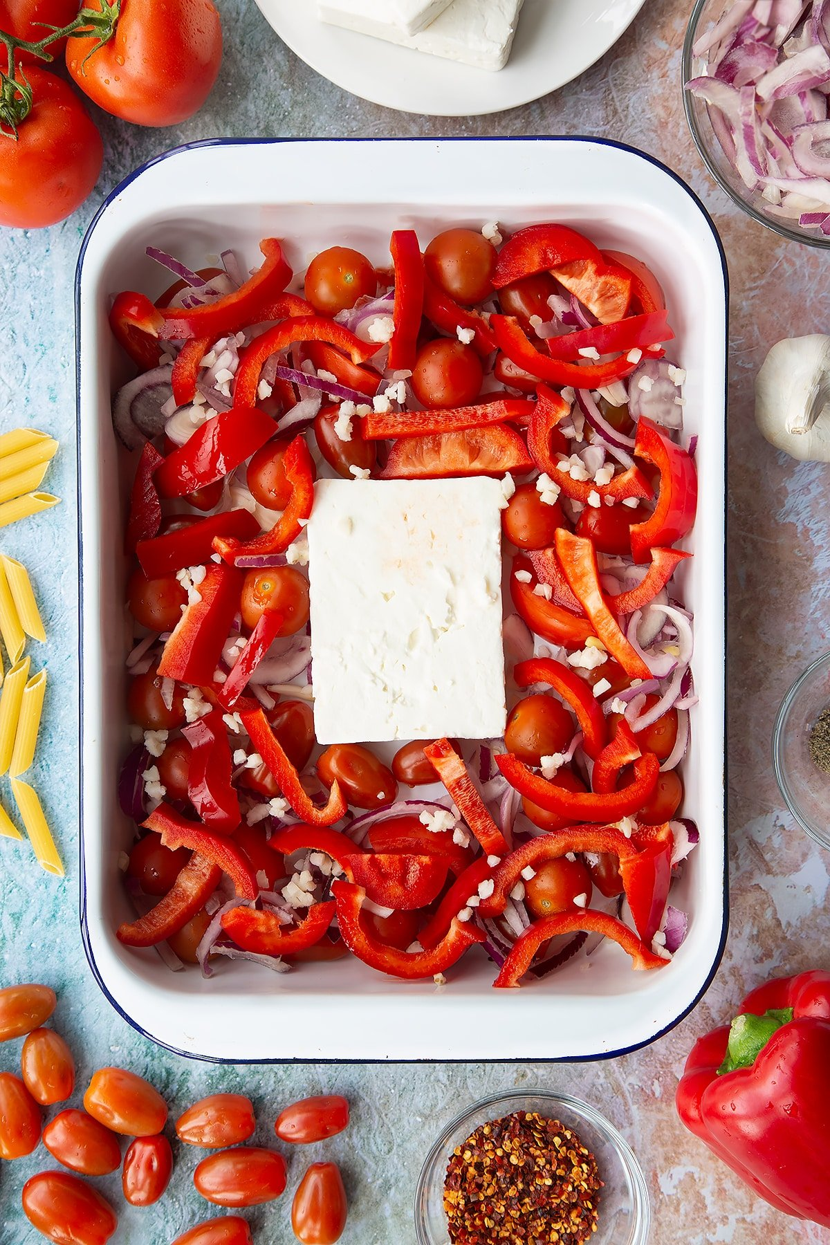 A block of feta surrounded by tomatoes, red pepper, red onion and garlic in a large white roasting tray. Ingredients to make baked feta pasta surround the tray.