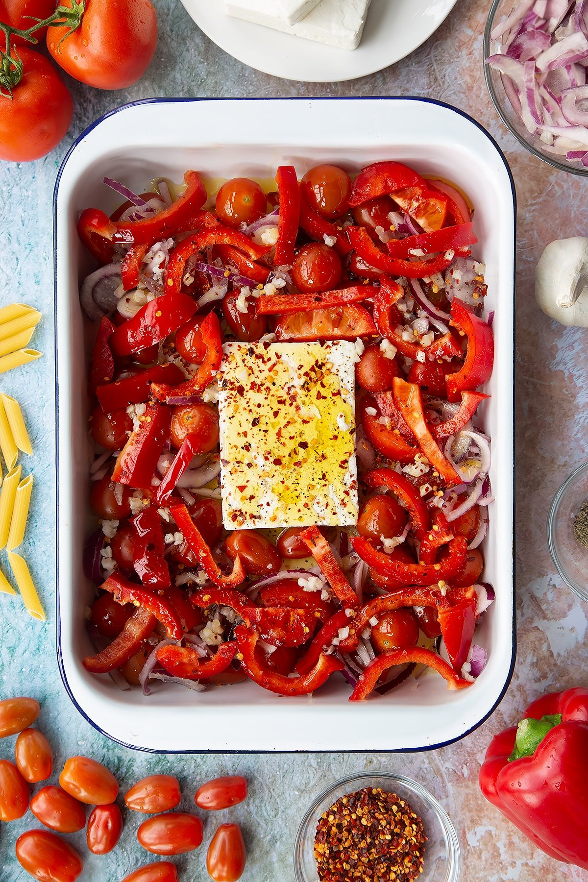 A block of feta surrounded by tomatoes, red pepper, red onion and garlic in a large white roasting tray, topped with olive oil, chilli flakes, salt and pepper. Ingredients to make baked feta pasta surround the tray.
