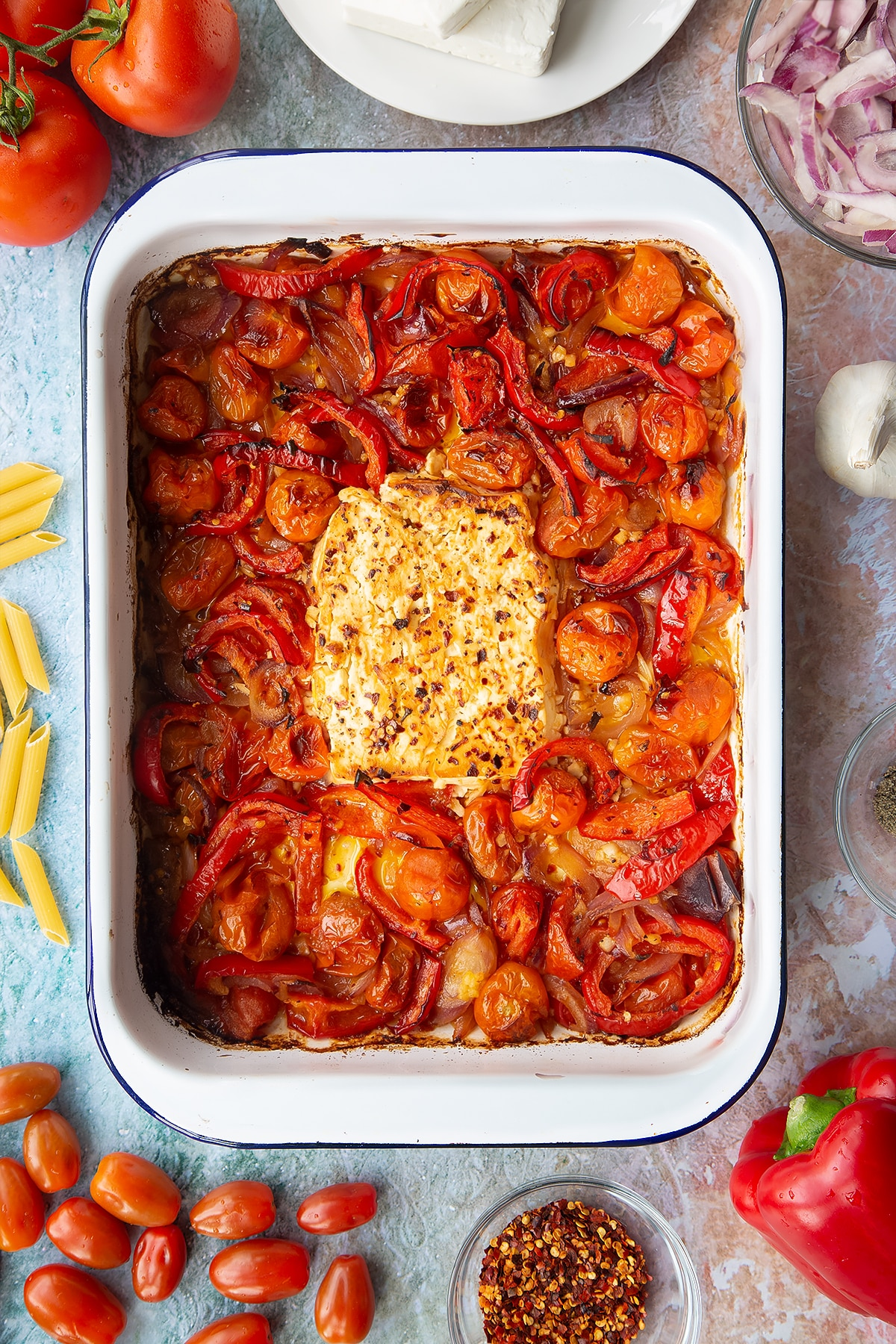 A block of baked feta surrounded by roasted tomatoes, red pepper, red onion and garlic in a large white roasting tray. Ingredients to make baked feta pasta surround the tray.