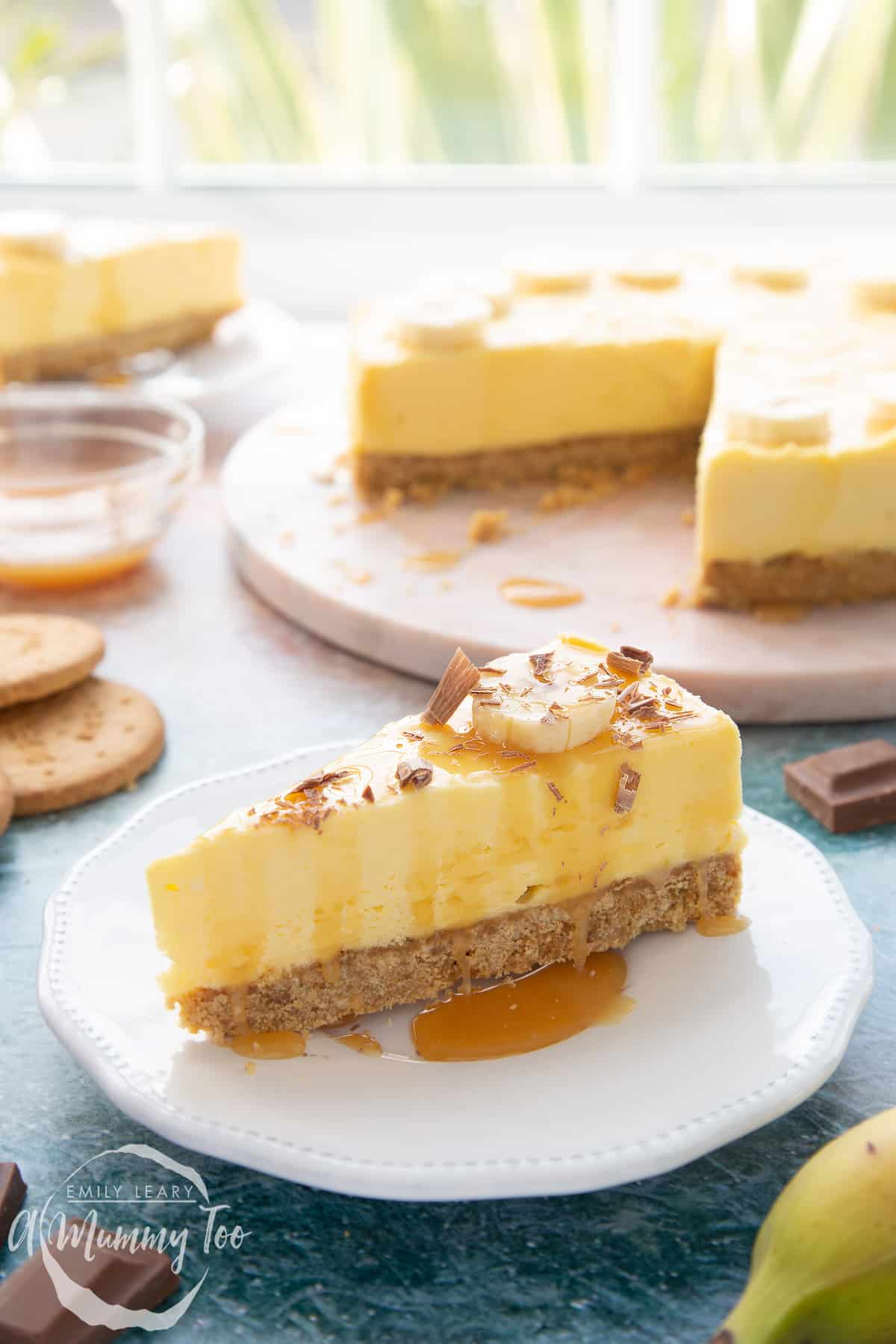 A slice of banoffee pie cheesecake on a white plate. It's drizzled with toffee sauce.