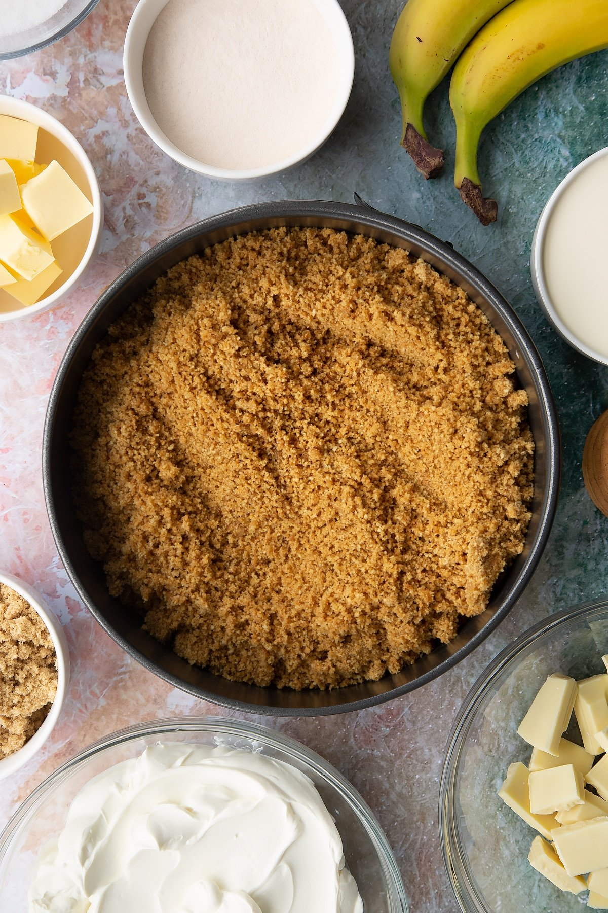 Crumbled biscuits and melted butter mixed together and tipped into a large cake tin. Ingredients to make banoffee pie cheesecake surround the tin.