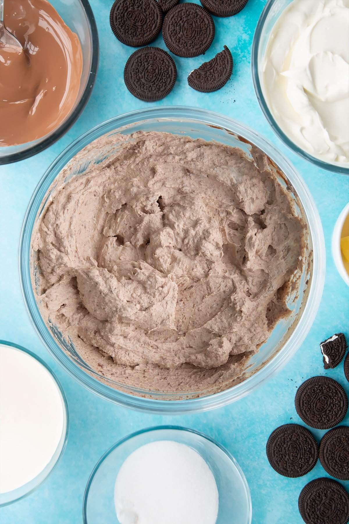 Overhead shot of whipped ingredients mixed with melted chocolate in a large clear bowl
