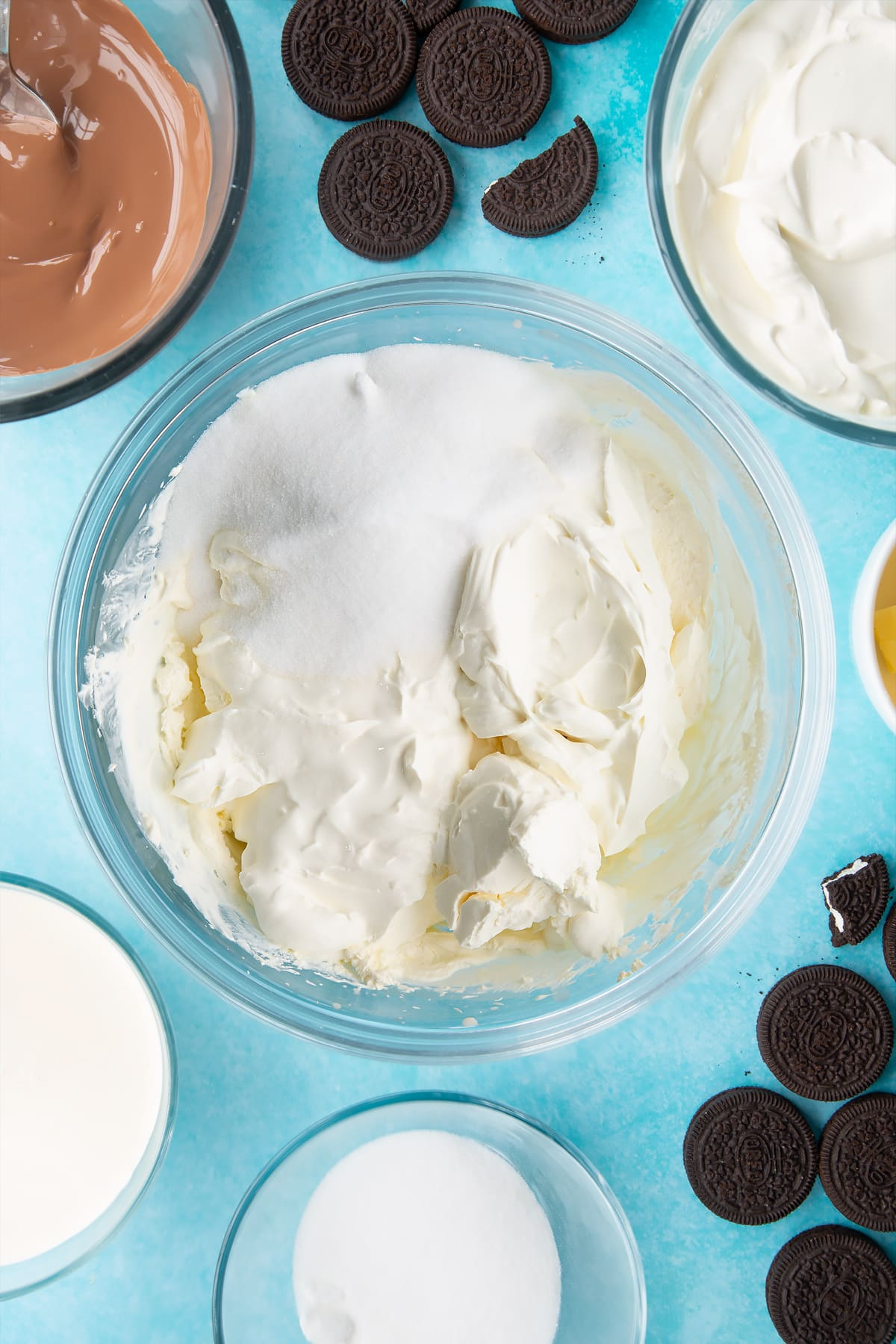 Overhead shot of whipped cream, cream, sugar and cream cheese in a large clear bowl
