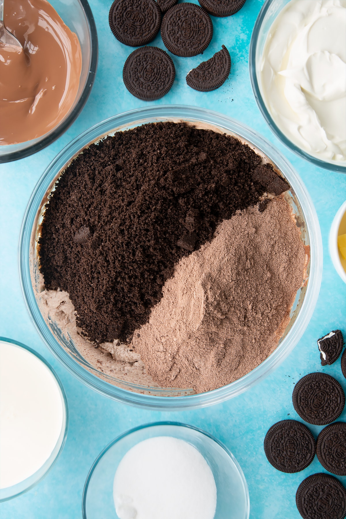 Overhead shot of whipped mixture, orea crumb and cocoa powder in a large clear bowl