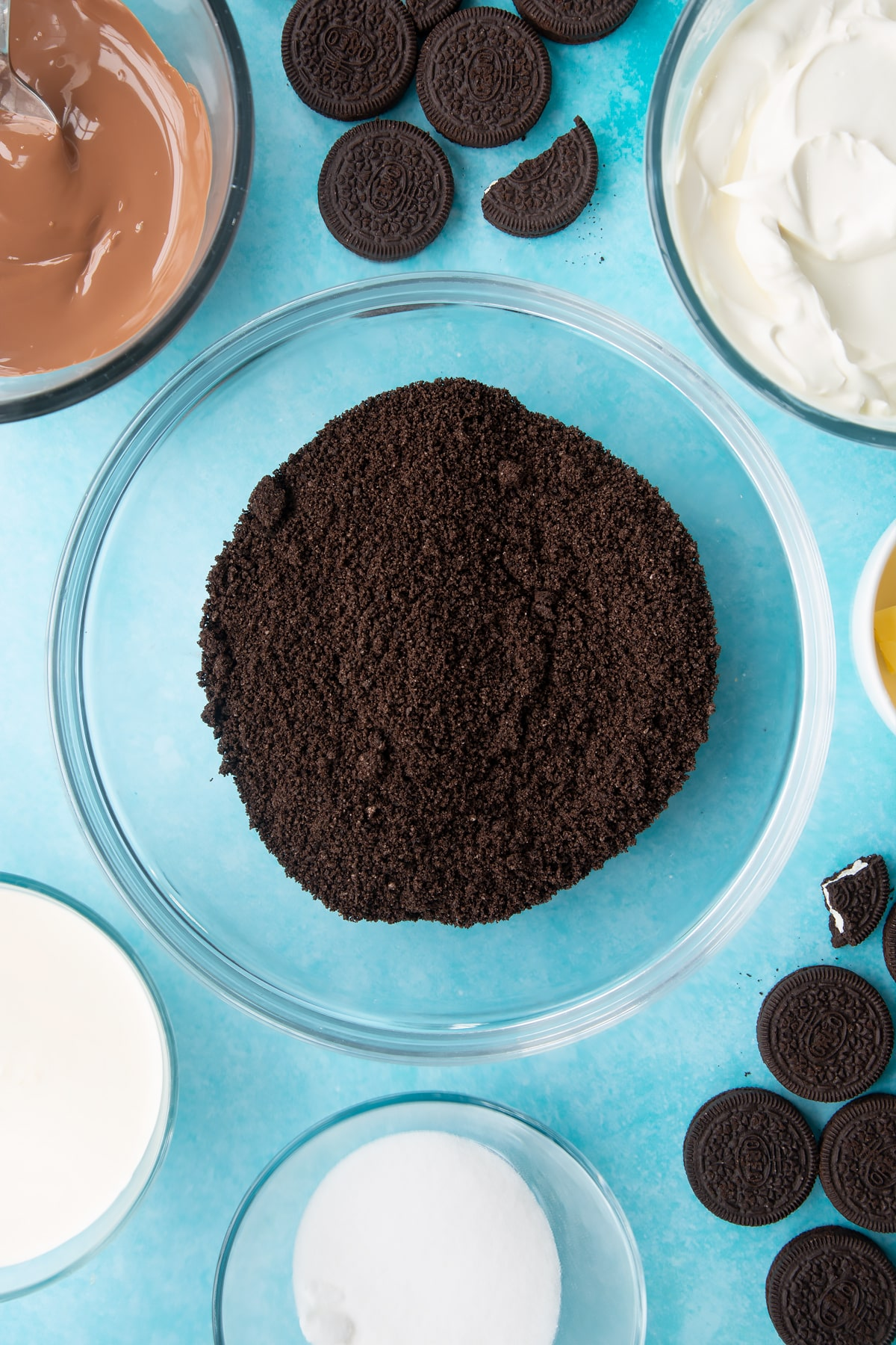 Overhead shot of oreo biscuits crumbed in a large clear bowl