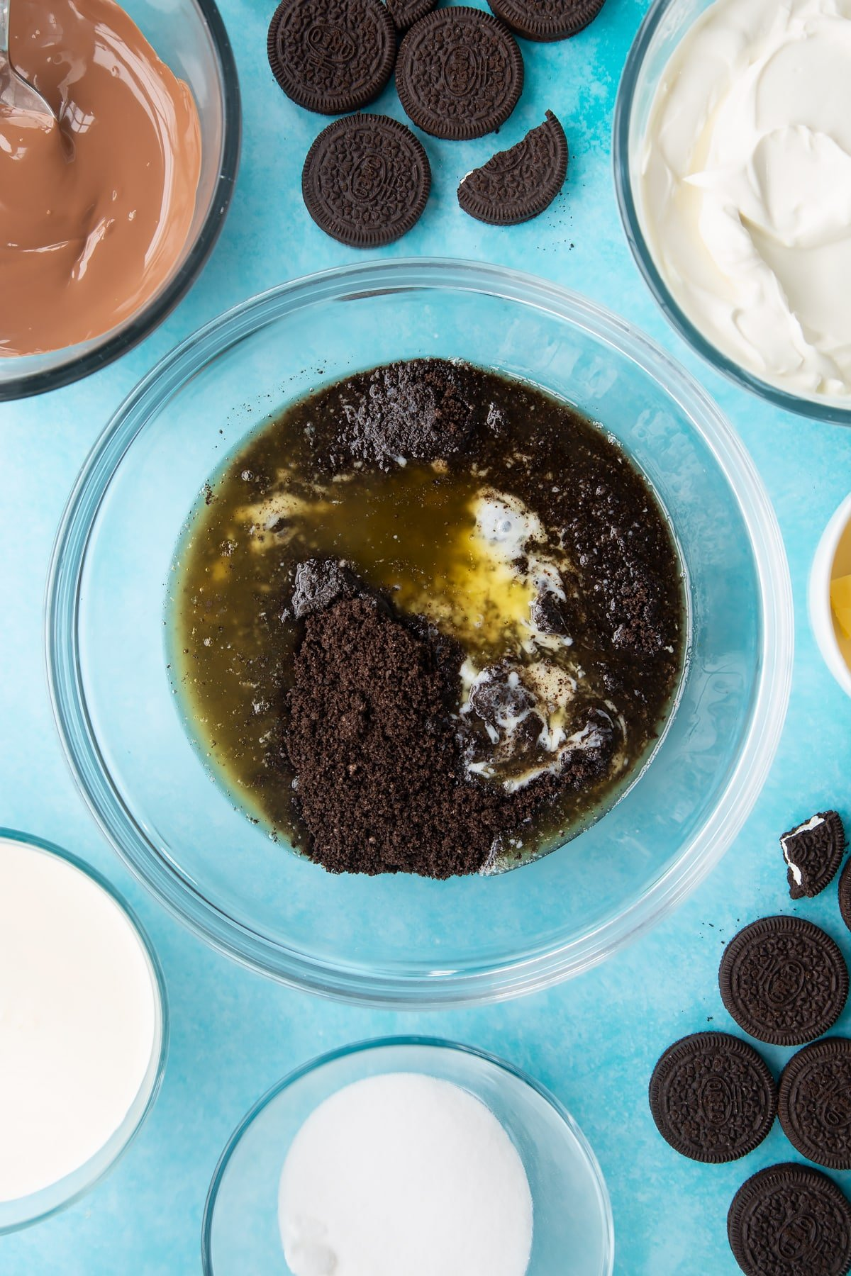 Overhead shot of oreo biscuits crumb with melted butter in a large clear bowl