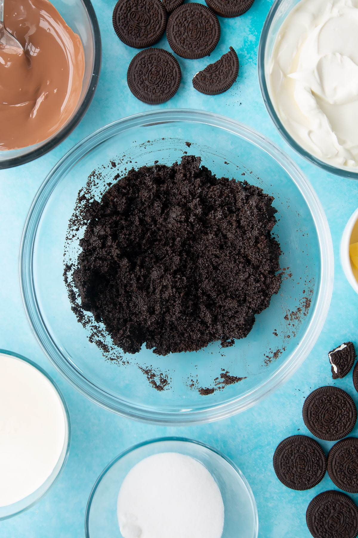 Overhead shot of oreo biscuits crumb with melted butter mixed together in a large clear bowl