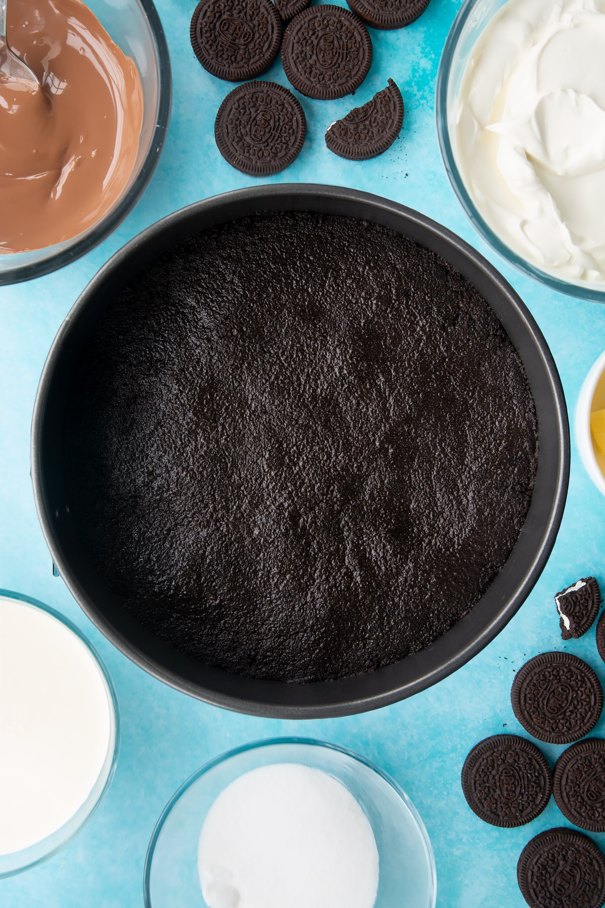 Overhead shot of oreo biscuits crumb pressed down in a large cake tin