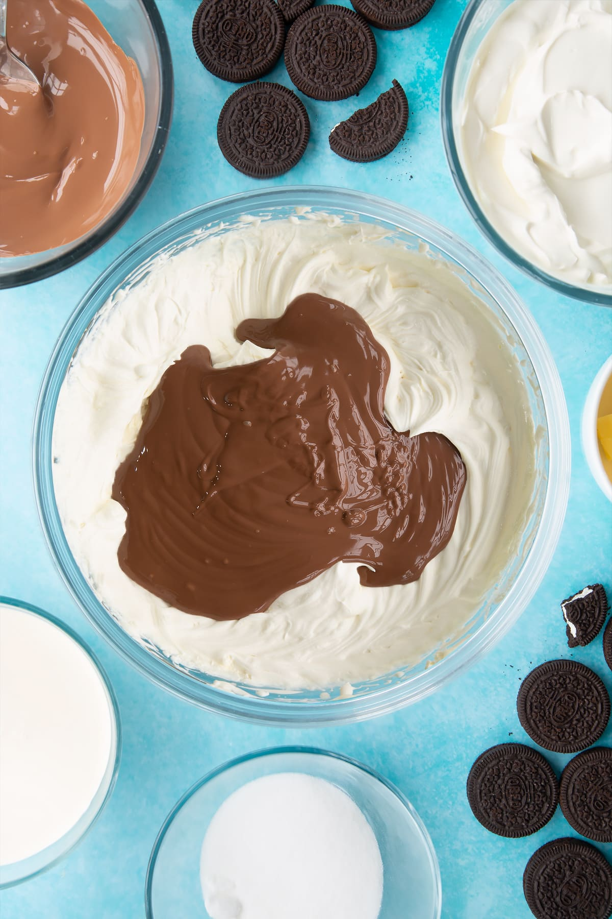 Overhead shot of whipped ingredients with melted chocolate in a large clear bowl
